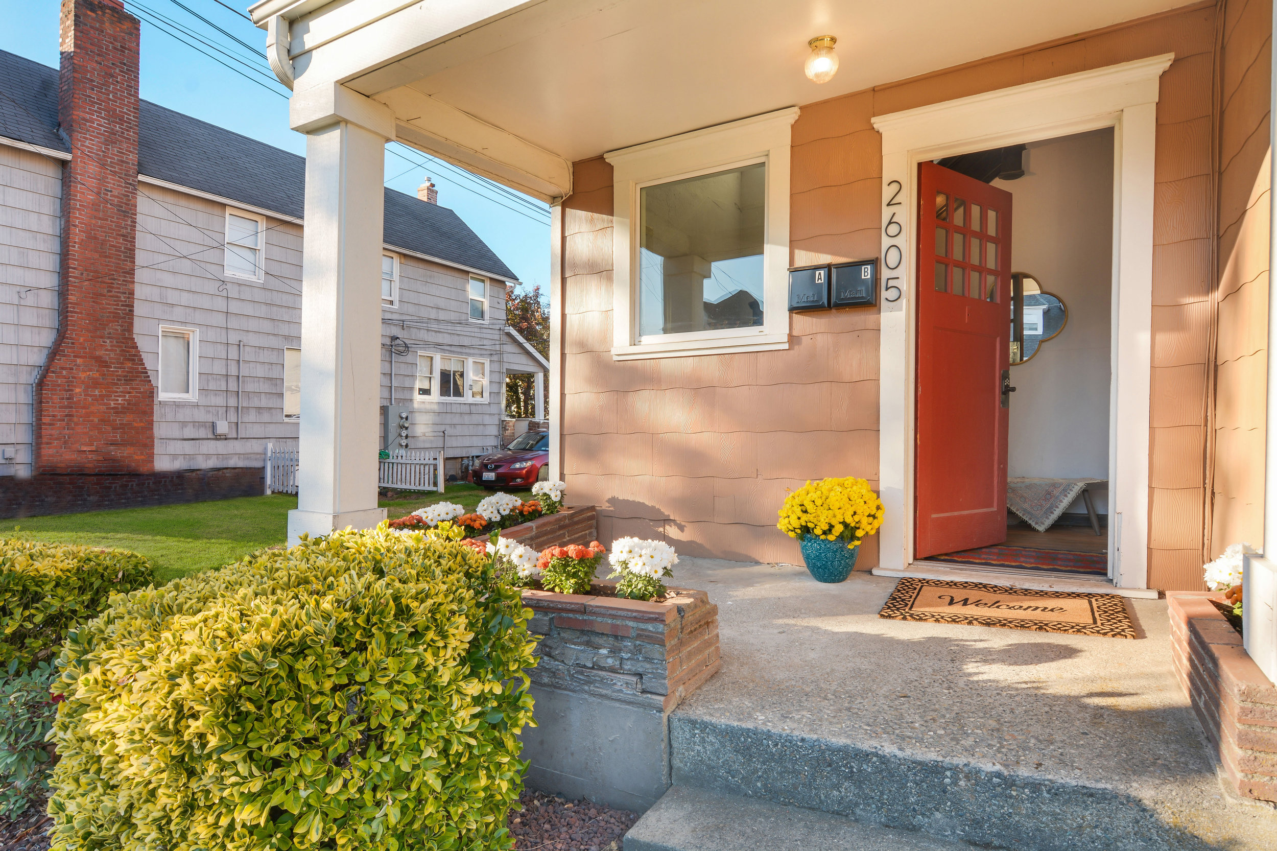 Covered front porch with flower boxes and shared entry for the 2 units inside this home.