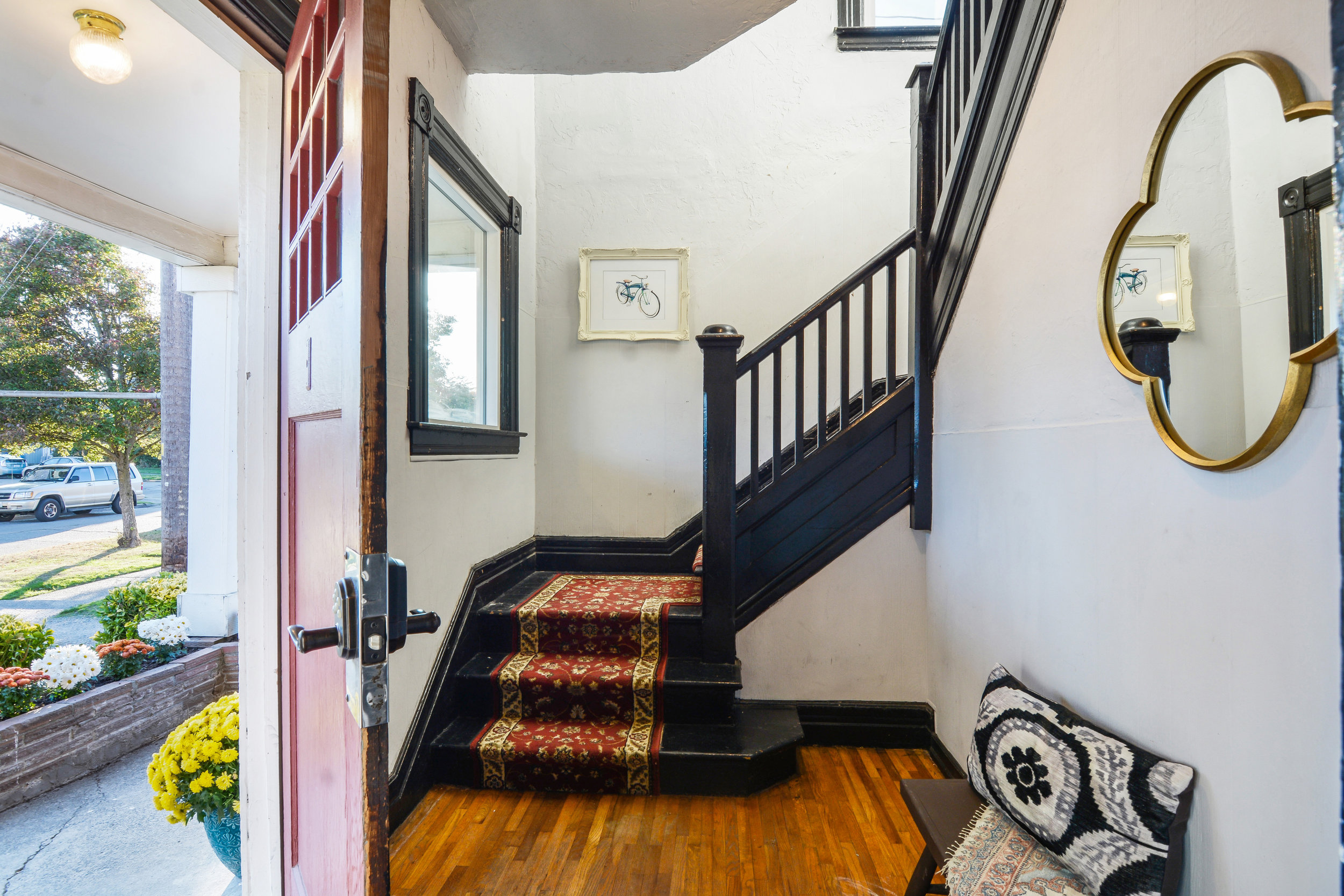 From the front porch step into the shared entry space with its hardwood floors, open staircase, and high ceilings.