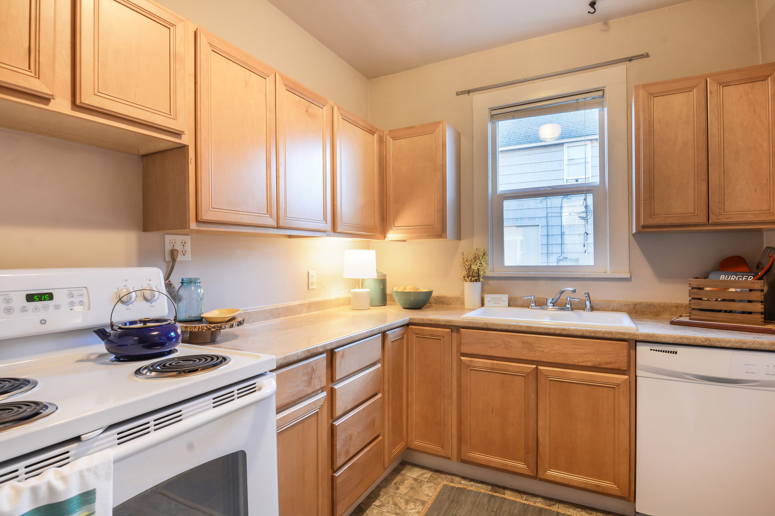 Wooden cabinets, a window facing west over the sink, and easy to clean vinyl floors complete the kitchen.