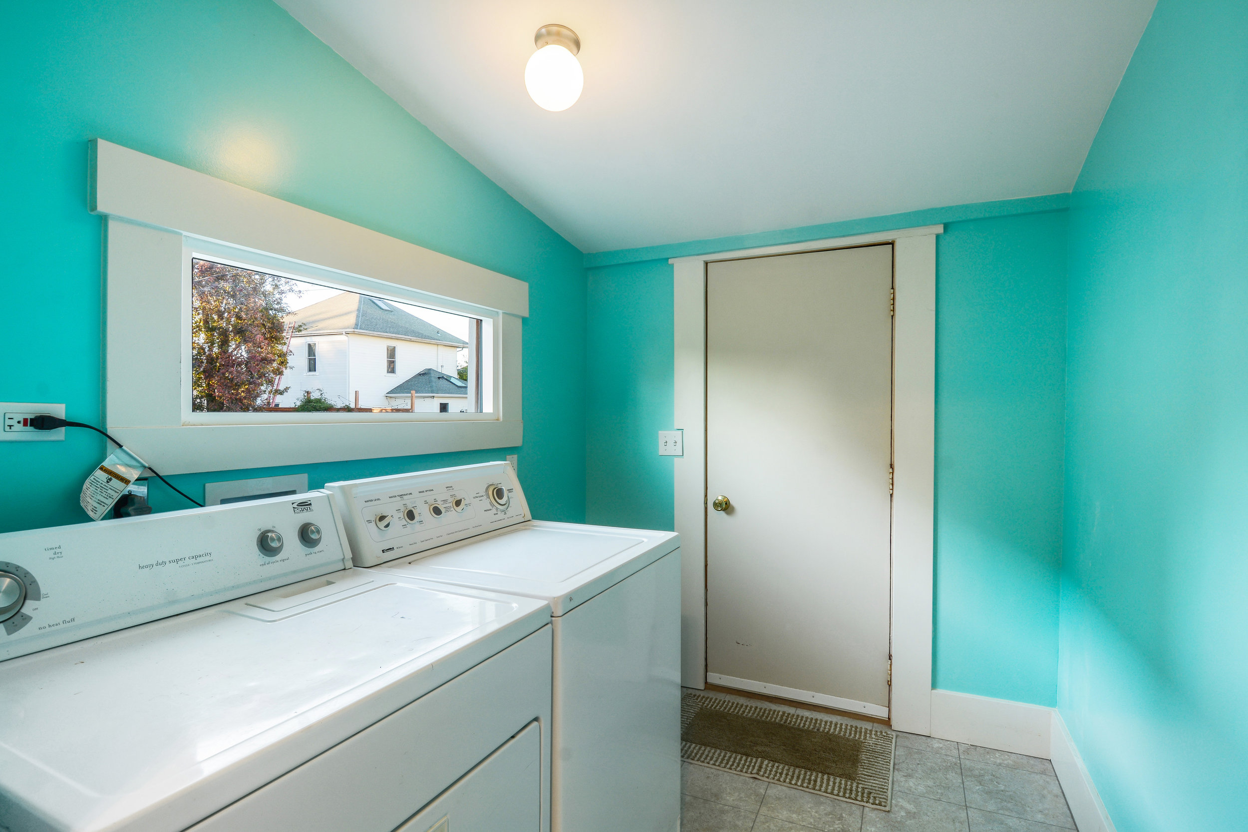 The main floor apartment includes this laundry room entered from the kitchen. The back door exits to the parking area at the back of the lot.