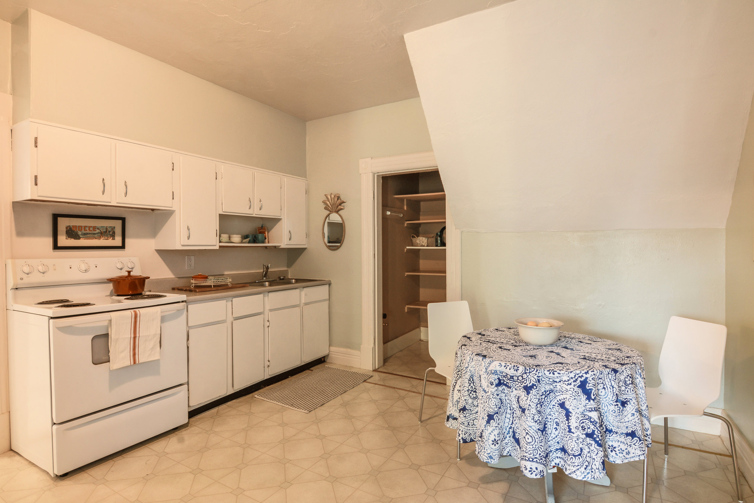 The second floor eat-in kitchen has plenty of room for a table and chairs. There's a refrigerator, stove, pantry, and stainless double-sink.
