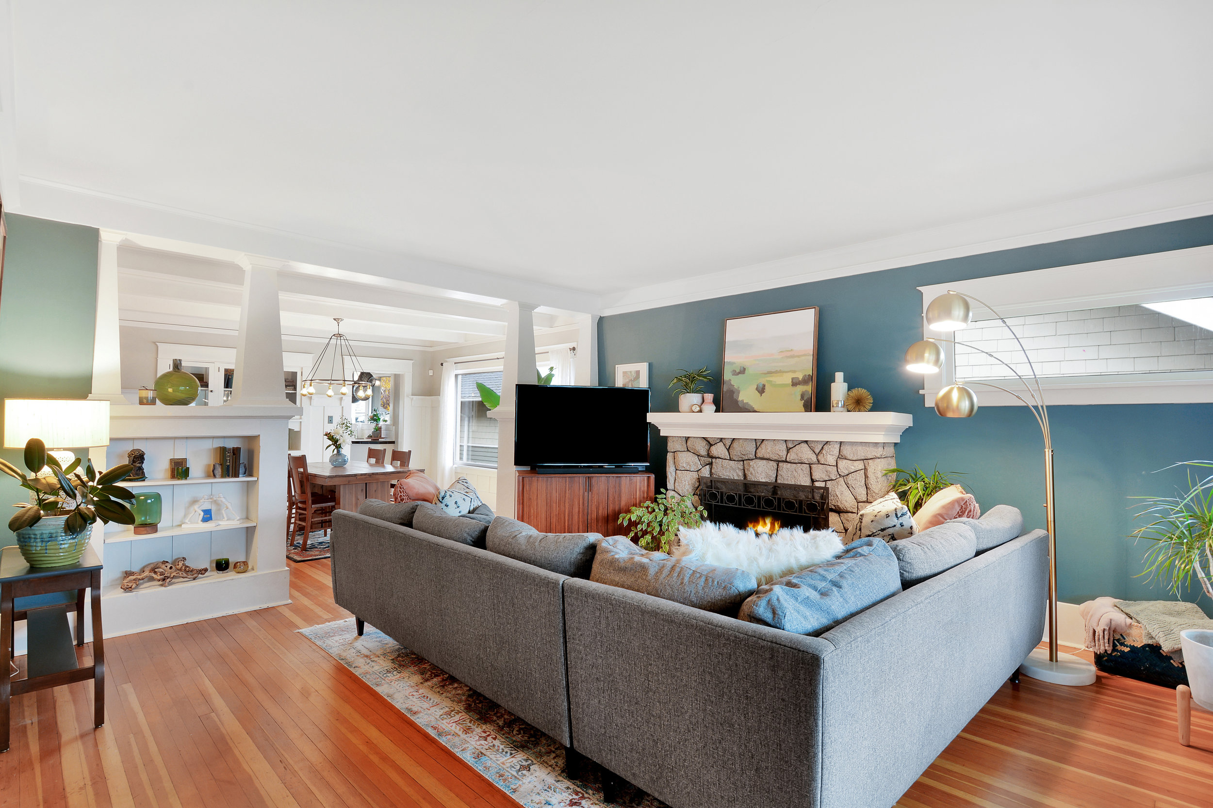 Another living room view featuring the oblong window and showing-off the colorful fir floors.