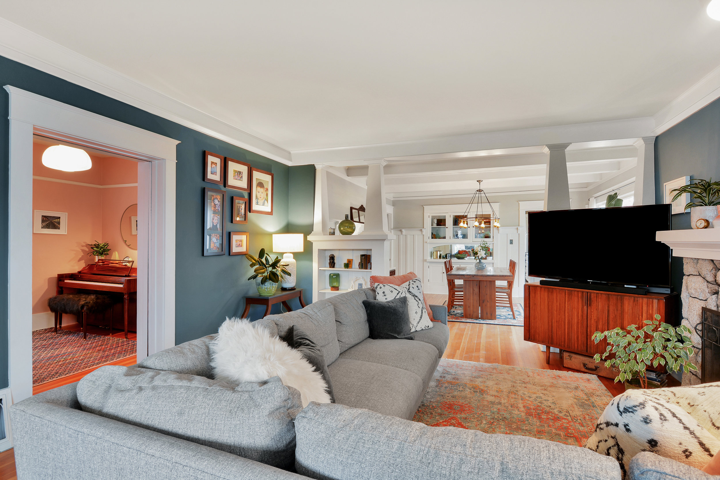 The living room (shown here with pocket door open) flows into the dining room. Notice the built-in shelves and picture rail.
