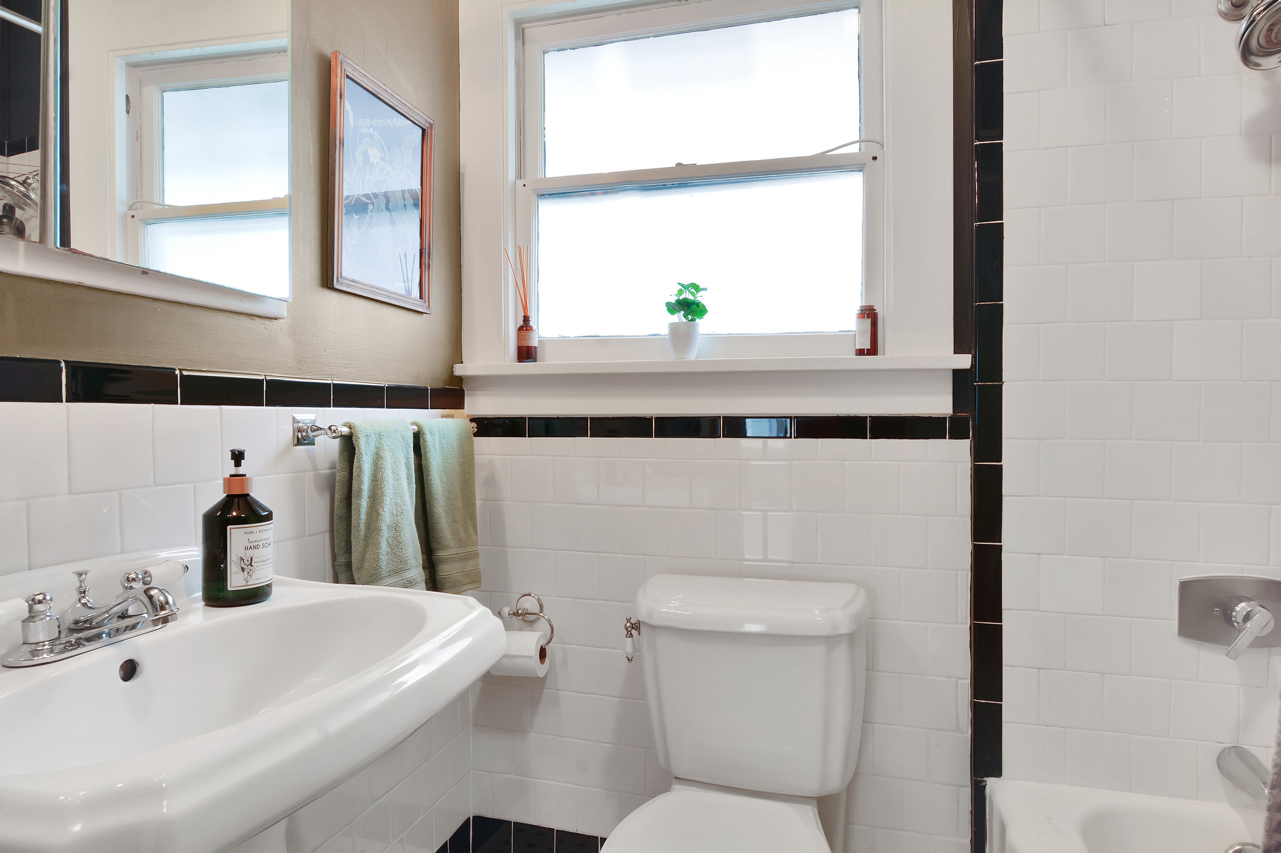Main floor full bath with black and white tile, pedestal sink, shower/tub combo, and medicine chest mirror.