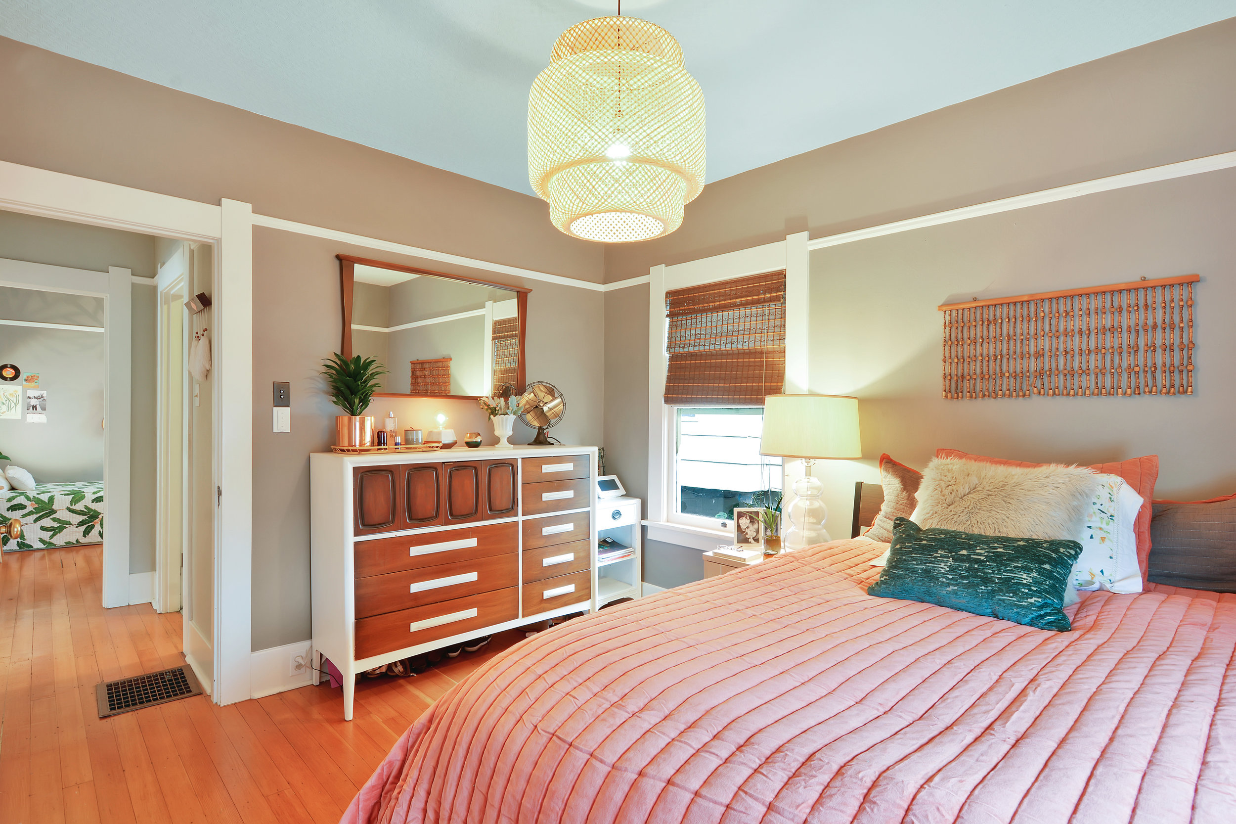 One of three main floor bedrooms featuring fir floors, wide trim, picture rail, and warm neutral tones.