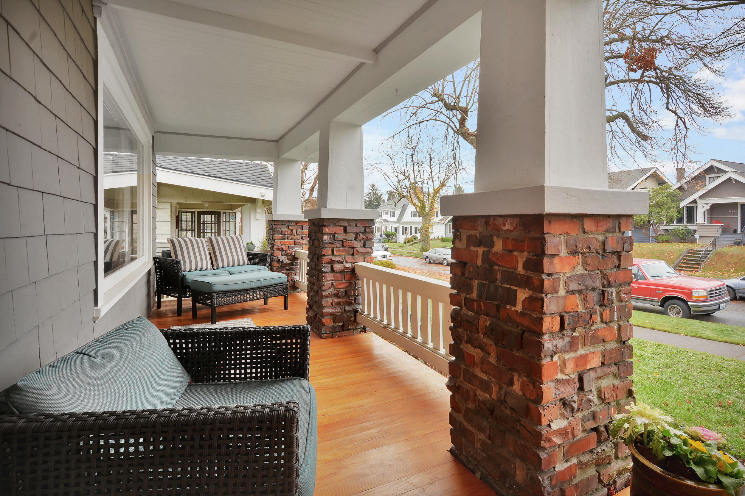 Brick and wooden pillars support deep eaves covering the porch across the front of the home.