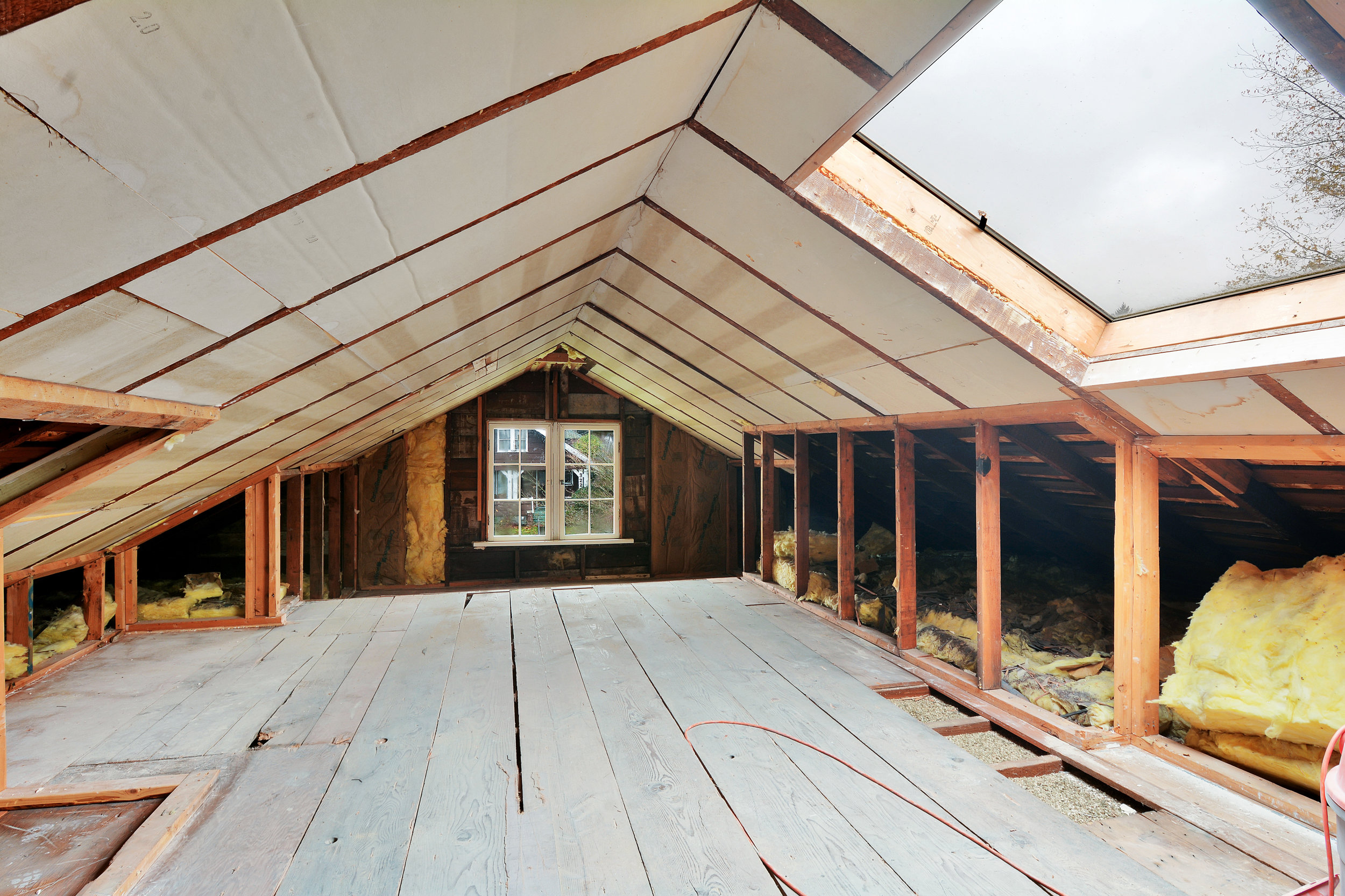 An unfinished attic with skylight and a window at each end. Accessible by stairs.