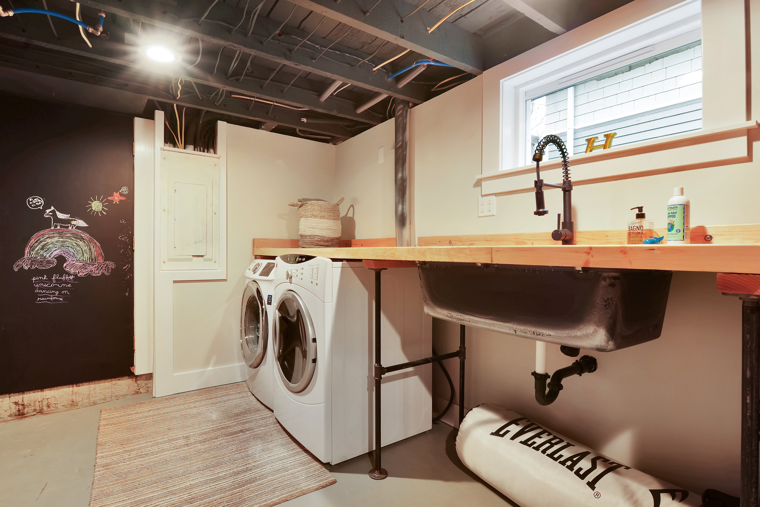 Basement laundry with counter, utility sink, and a chalkboard door leading to the back yard.