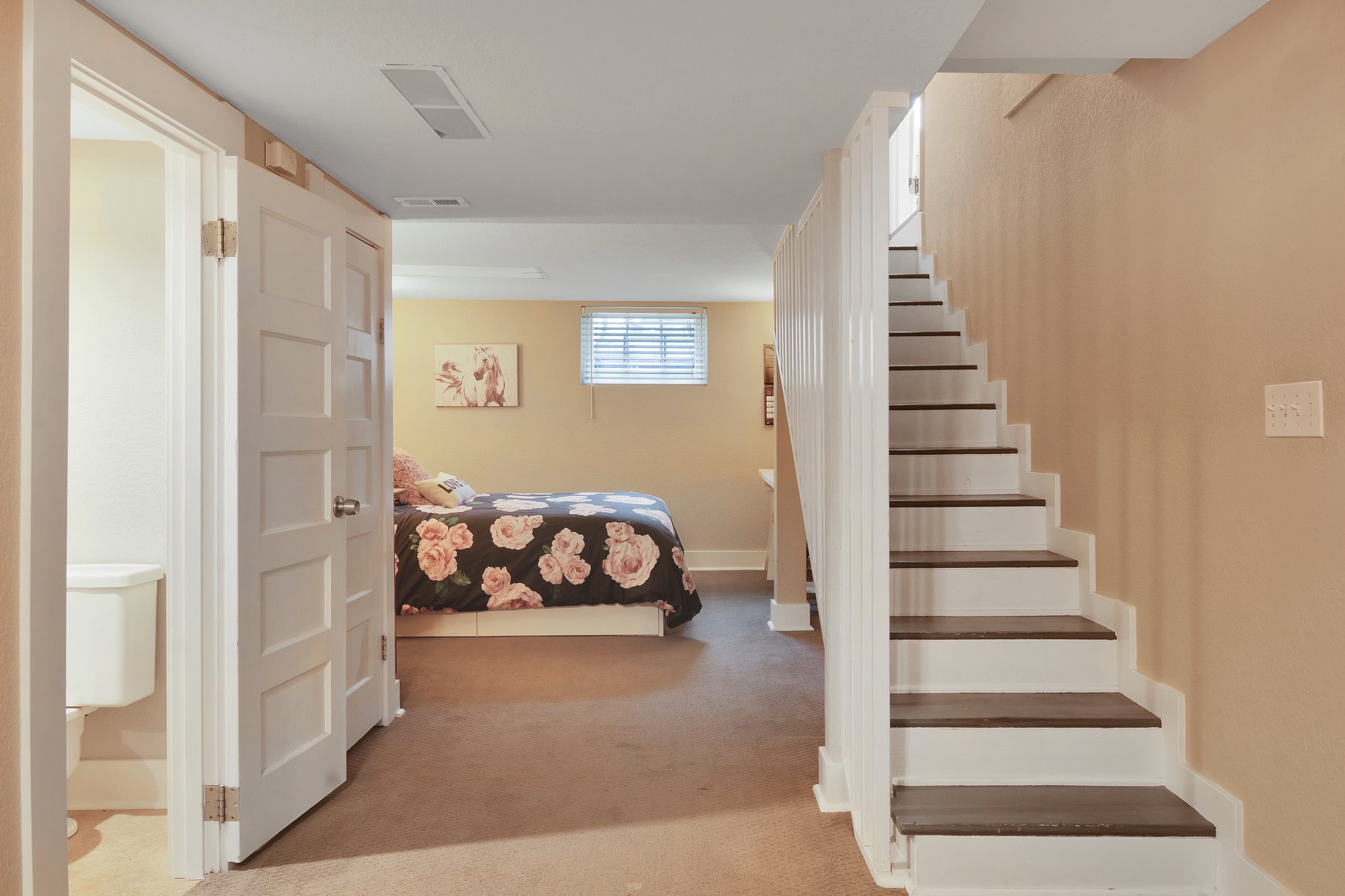 The finished basement offers additional living space and flexibility to the home. Notice a half bath on the left.