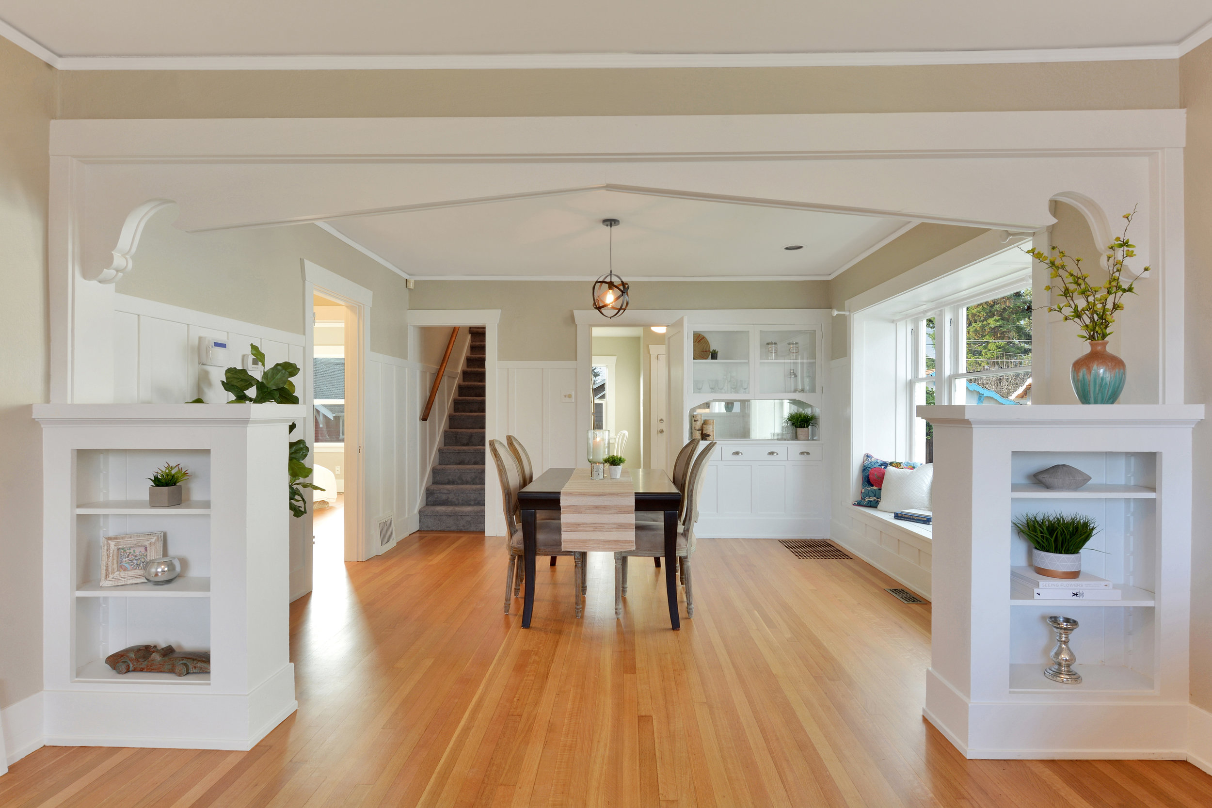 A decorative arch connects the living to the dining room with its wainscoting, built-in buffet, window seat, and refinished oak floors.