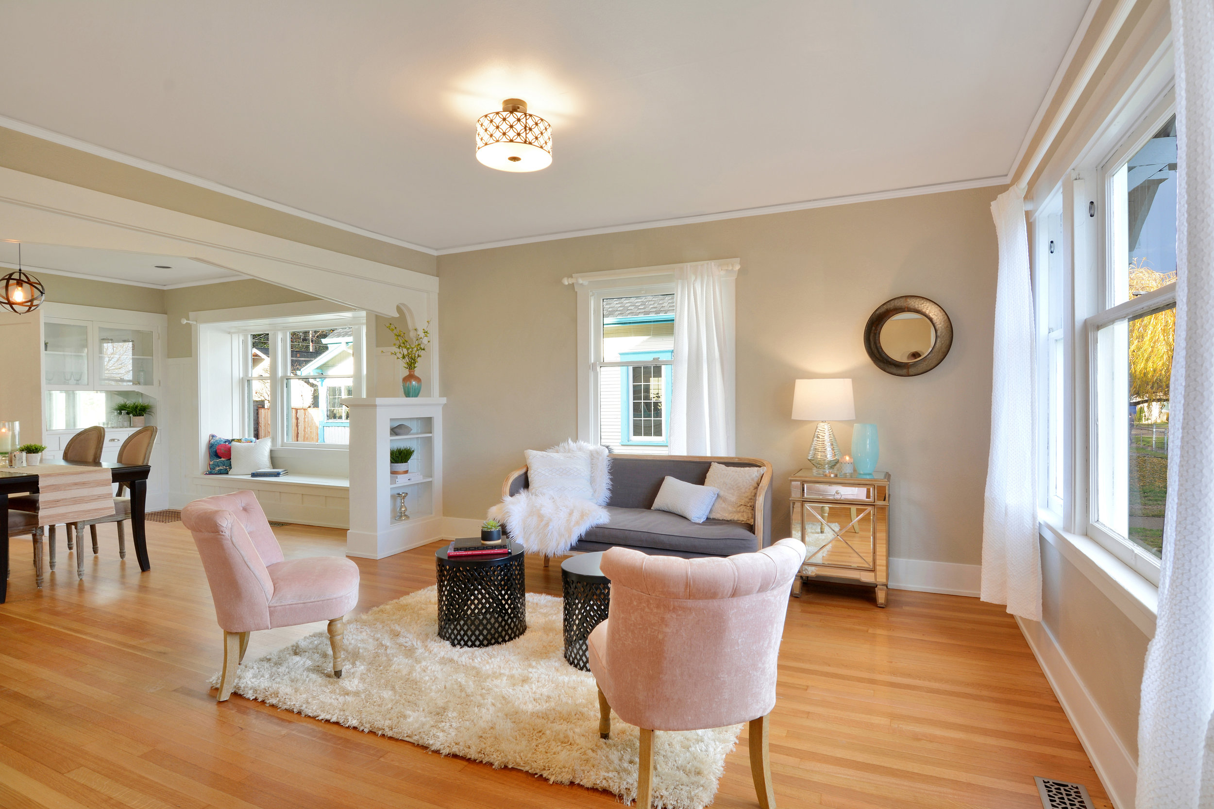 Refinished oak floors extend through the living room with its big windows, built-in shelves, and crown molding.