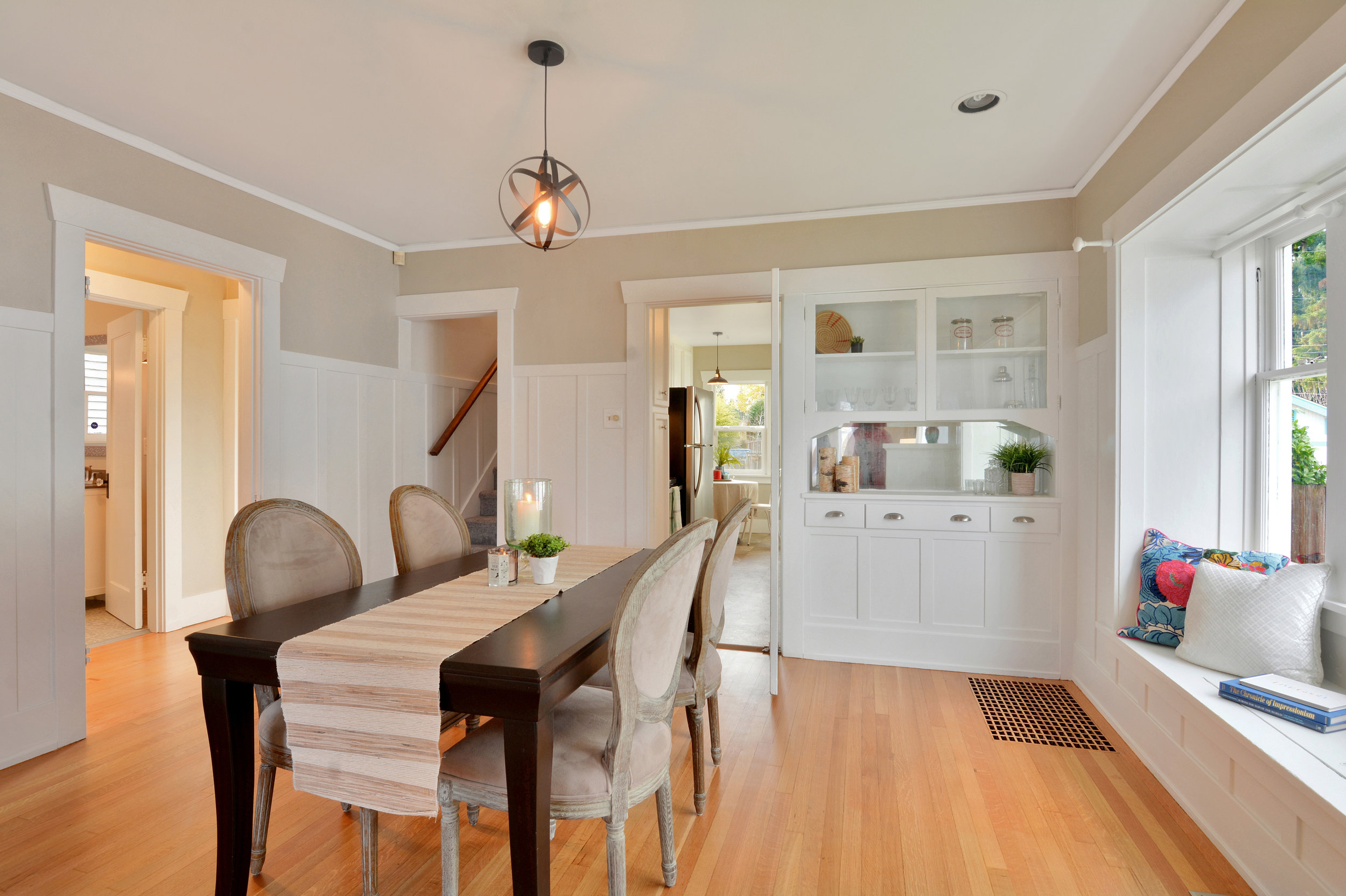 This spacious dining room opens into the main floor hallway on the left, the stairwell to the upper floor, and opens into the kitchen (or the door may be closed if desired).