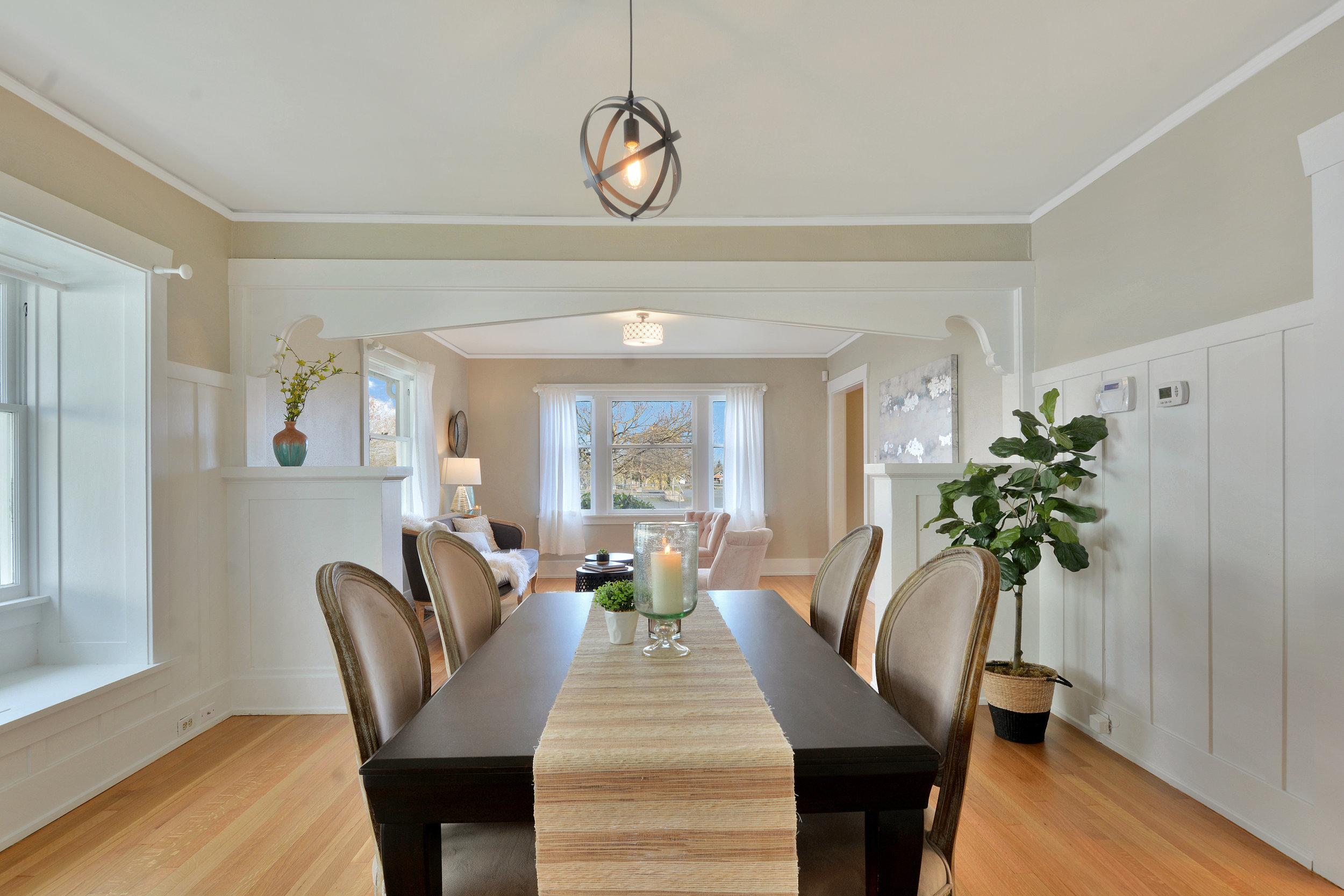 The dining room with its white wainscot, fresh paint, and beautiful oak floor as seen from the kitchen.