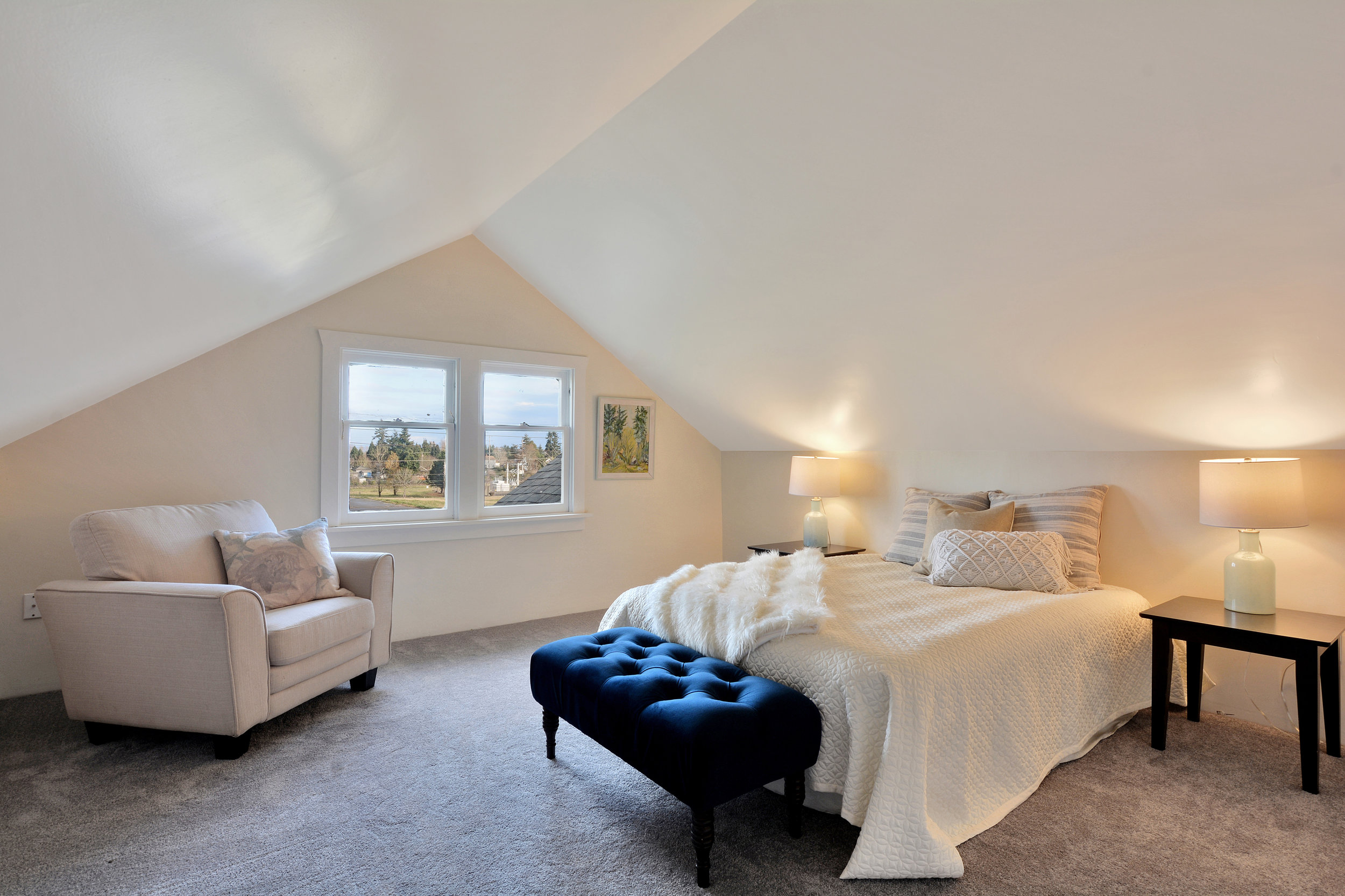 This third bedroom, located upstairs, is cozy with brand new carpet, sloped ceilings, and windows facing east for the sunrise.