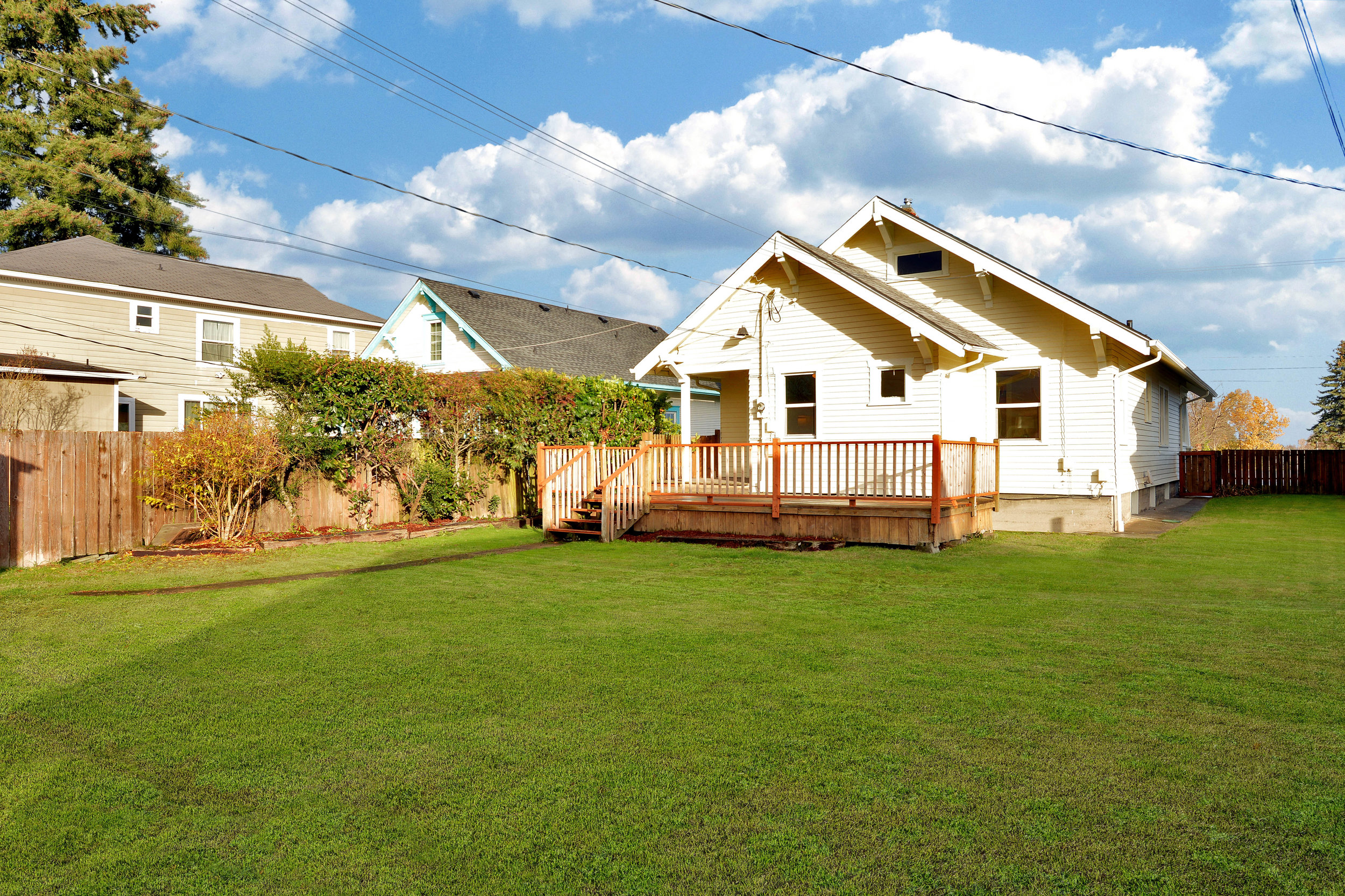 The fully-fenced back yard is big! There's room for flower beds, a vegetable garden, swings set, room for pets, and room to play.