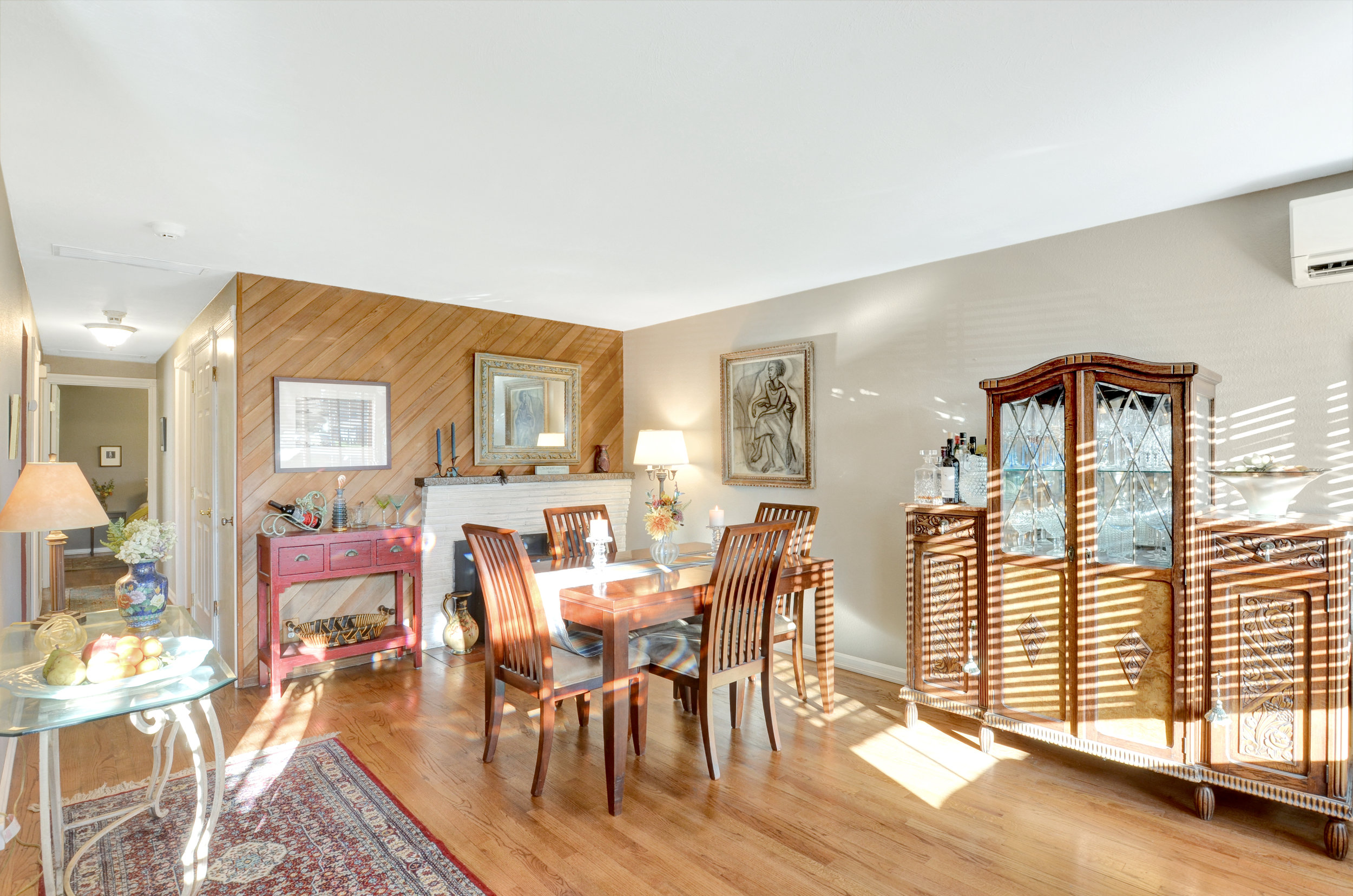 Another view of the living-dining area with its paneled wall, fireplace, and lovely light.