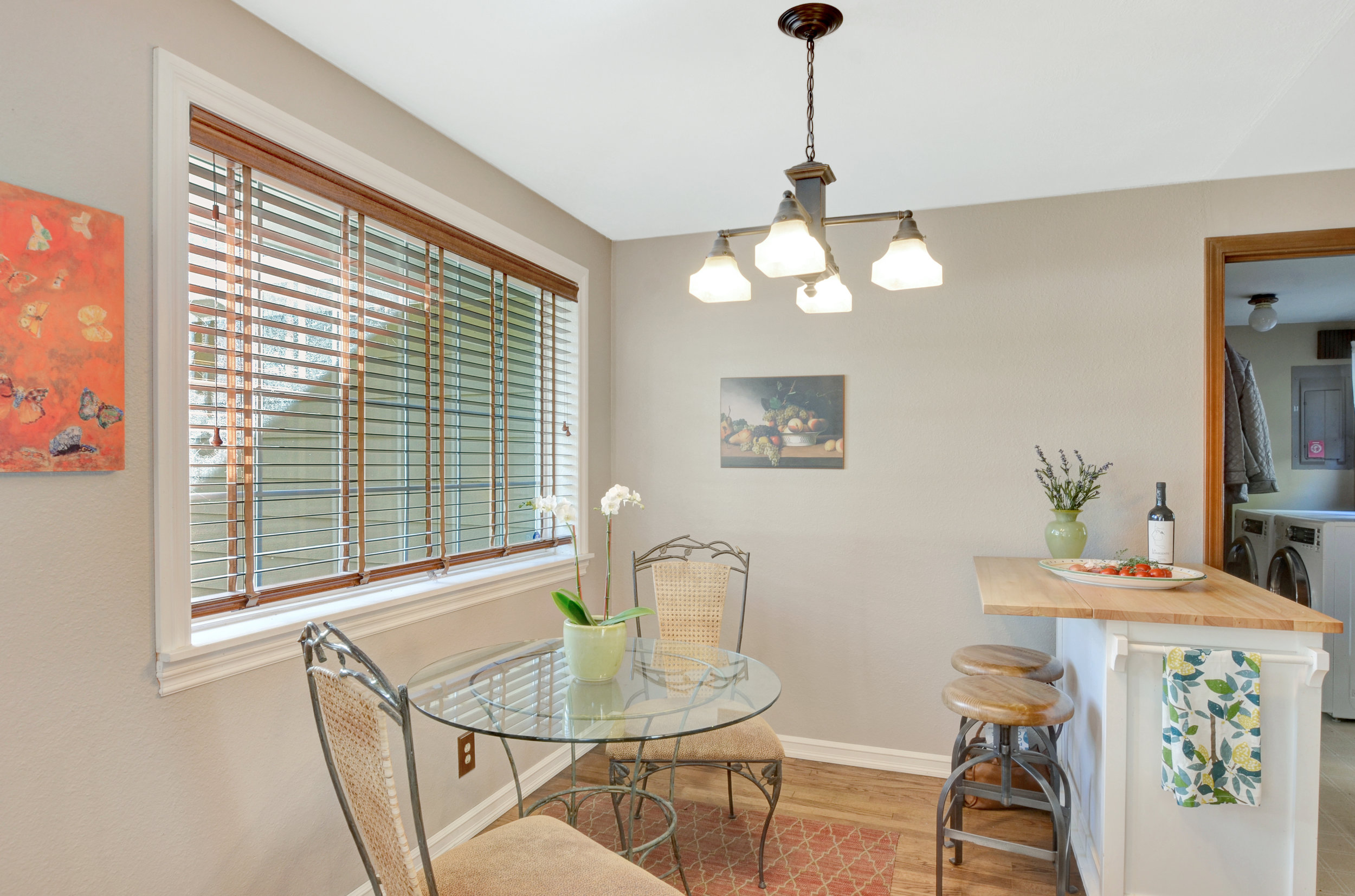 To the left of the front door, this area can be set up as the main dining area, or can be used as shown here with a mobile kitchen island and smaller breakfast table.