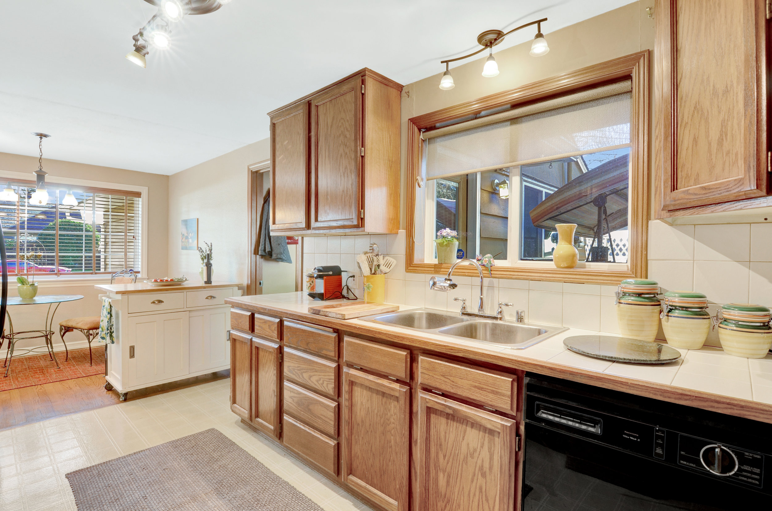 Tiled counter and backsplash, double stainless sink, and a good amount of cabinet storage. The full set of appliances stays.