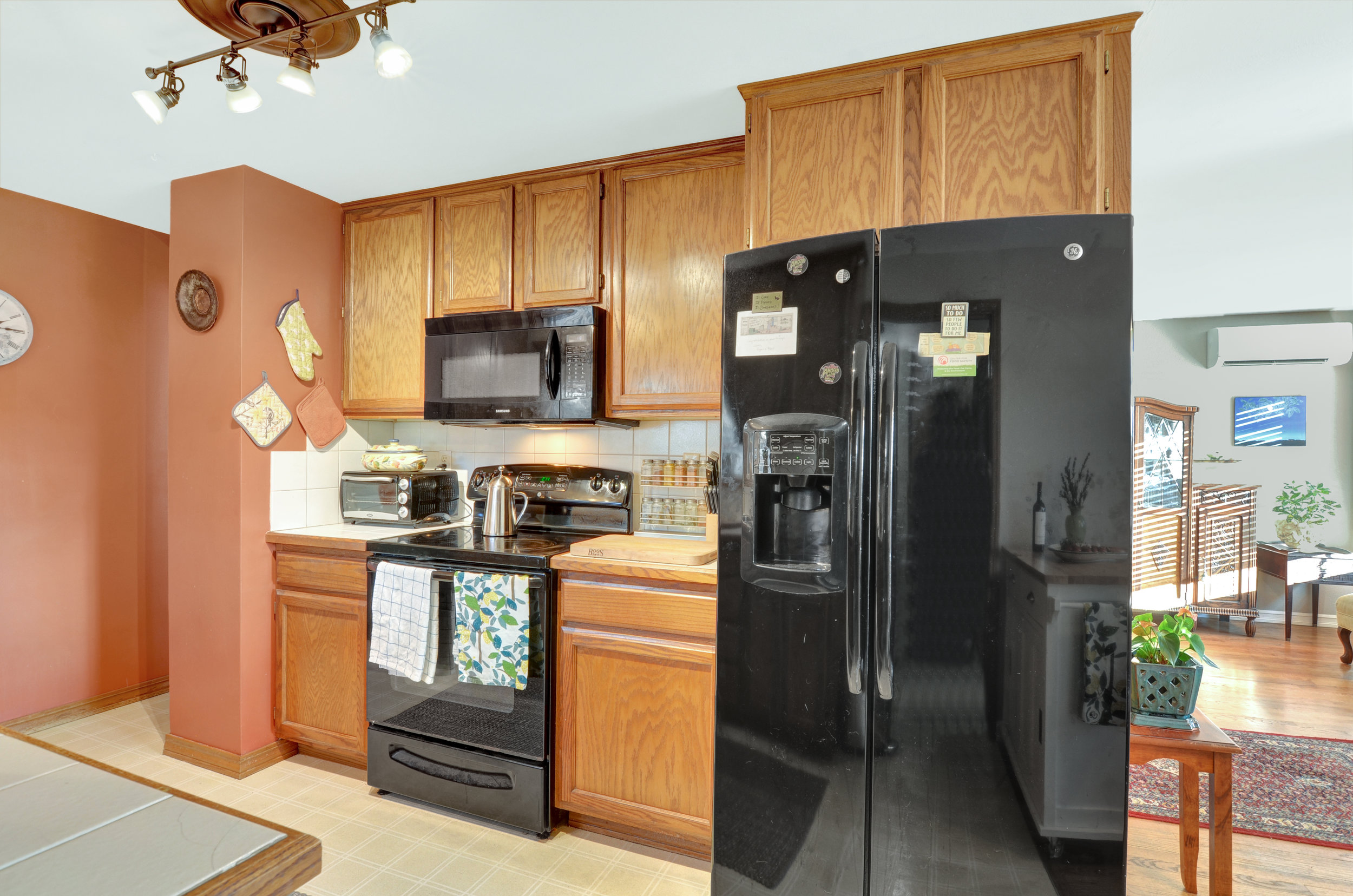 Side-by-side fridge, smooth top stove, and microwave (dishwasher is beside the sink). Turn right past the stove to enter the hallway at the end of the living room.