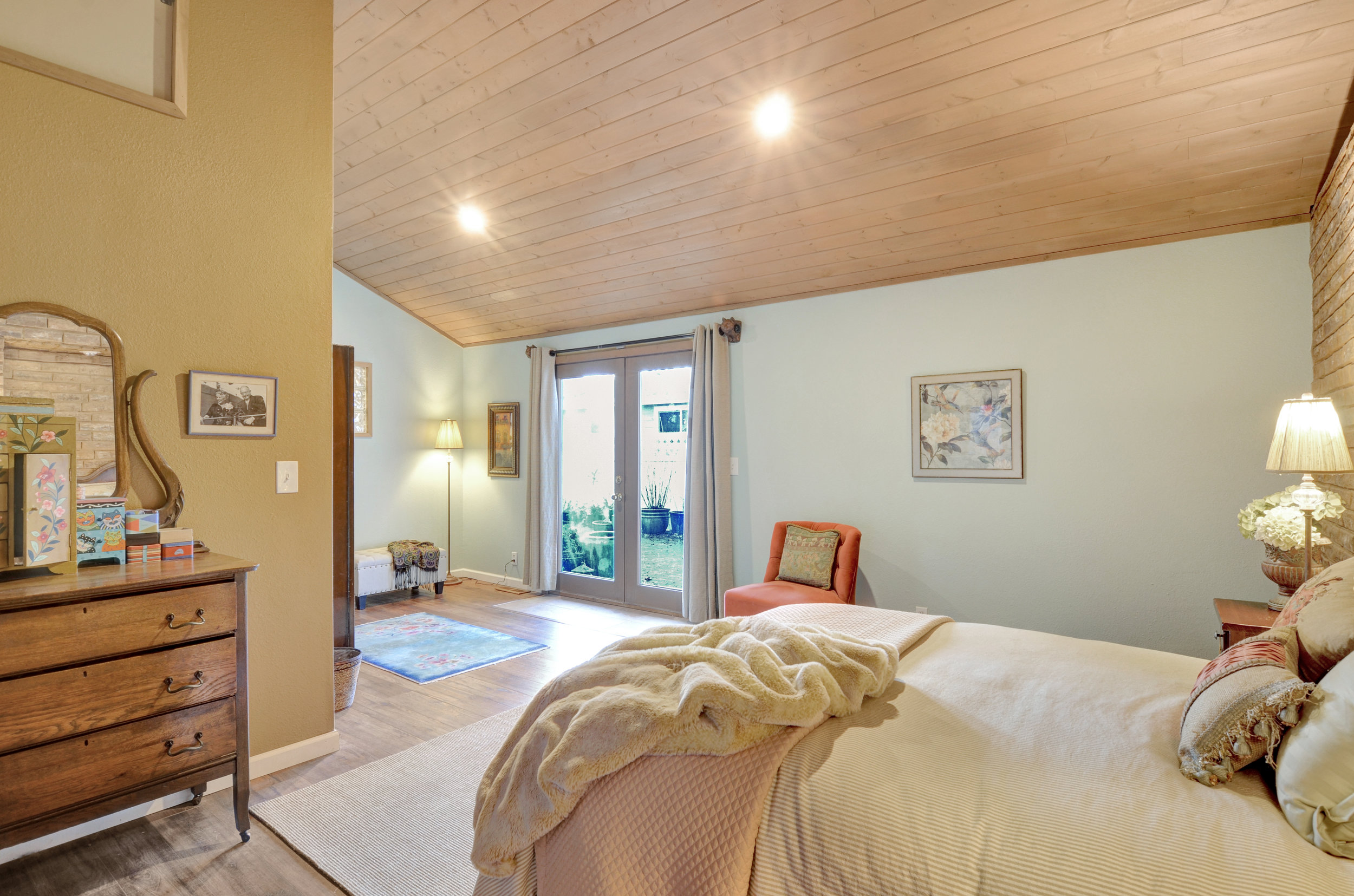 View from the corner of the bedroom to the French doors leading to the fully-fenced back patio.