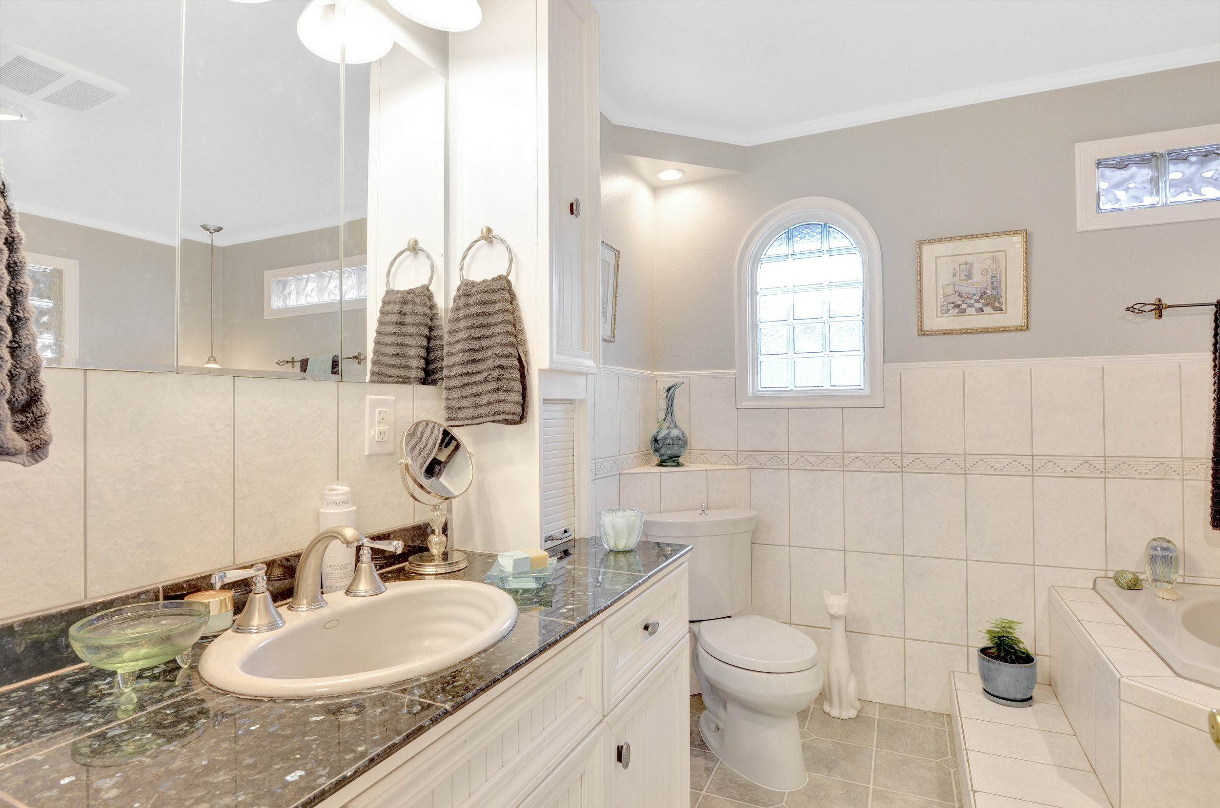 Full bath includes a tiled-in corner tub with Roman faucet, a separate stall shower, and large vanity with glass tile countertop.