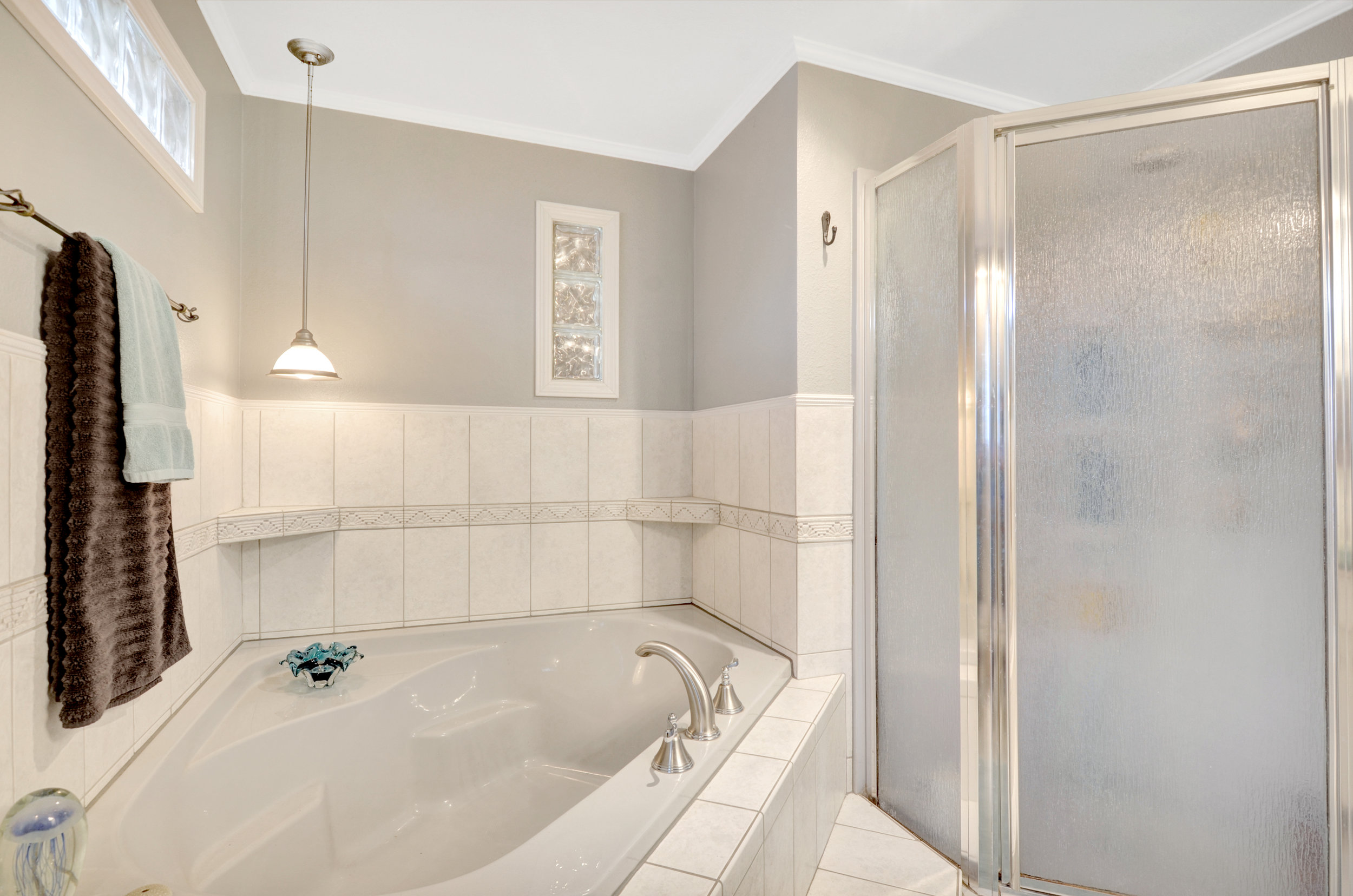 This is a tub for soaking! Privacy glass in the windows and a separate shower complete the room.