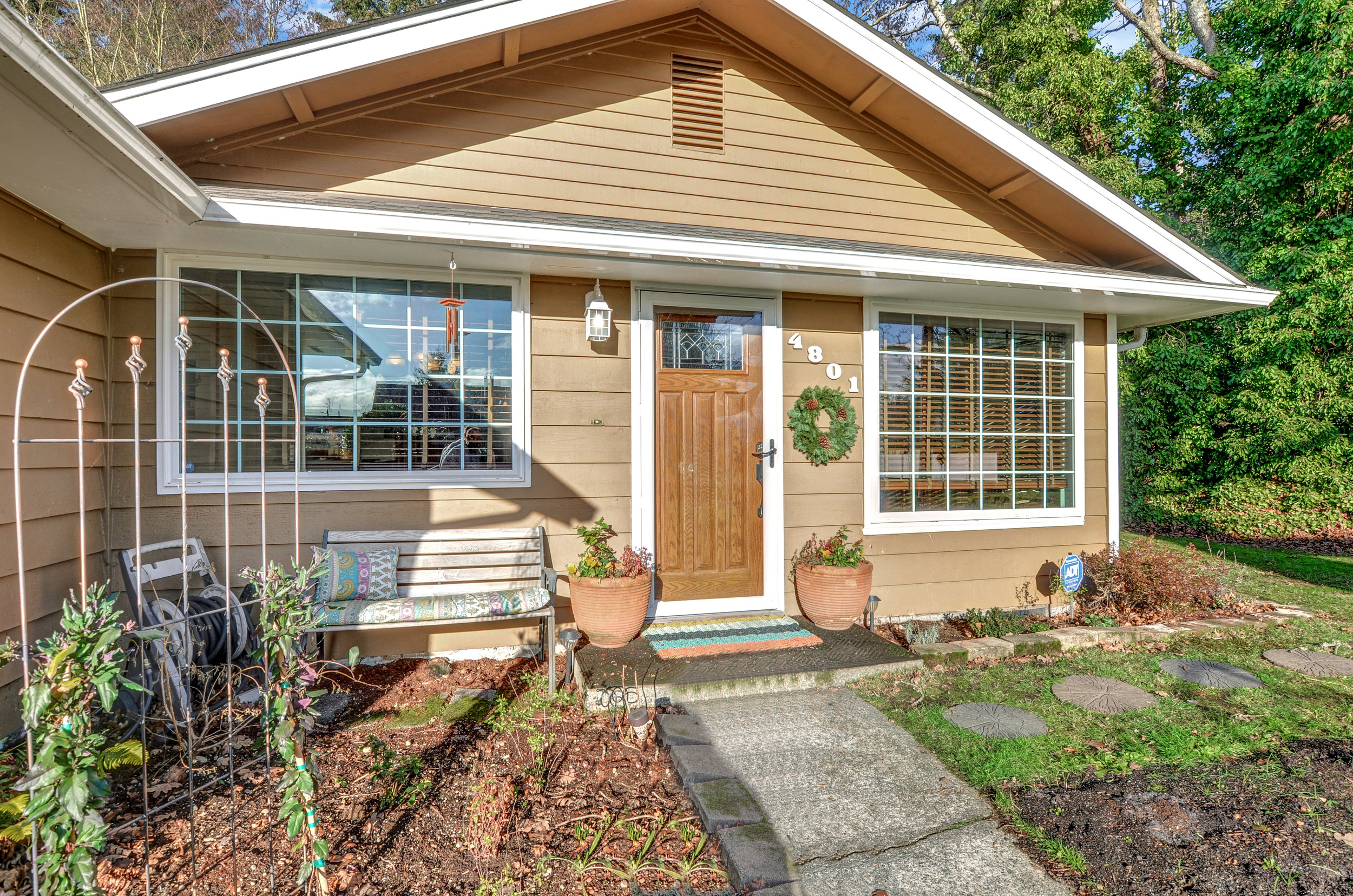 A paved path beside garden beds and lawn leads to the front door of 4801.