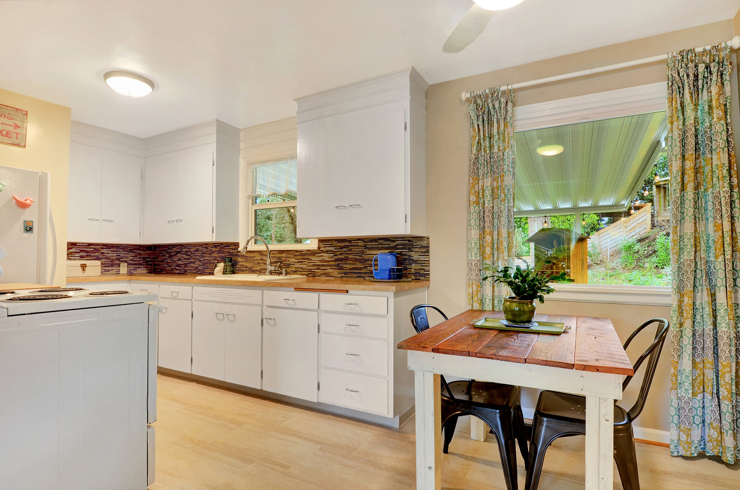 The dining area has a nice view to the back yard and flows seamlessly into the kitchen and living rooms. A sleek Minka Aire kitchen fan keeps the dining area bright and helps with airflow too.