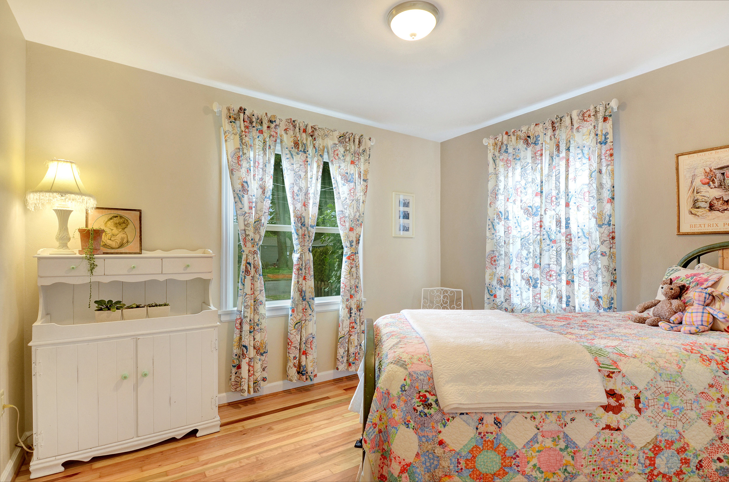 Just down the hall find the bedrooms with their refinished fir floors. This front bedroom is lit by big windows, a new LED ceiling light, and overlooks the front and side yards.