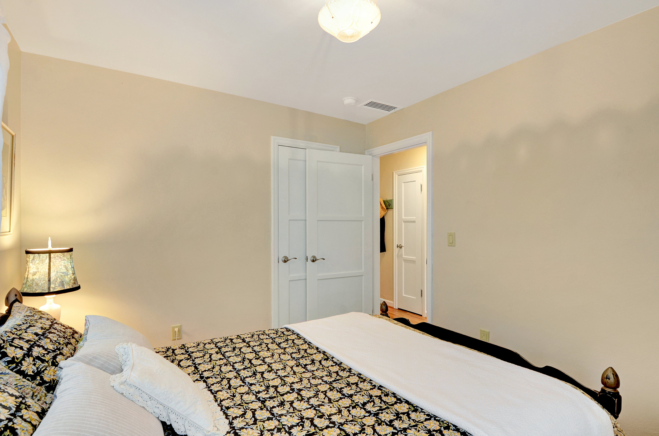 From the open door of this back bedroom, you catch a glimpse of the hallway with its additional closet, and room for a coat rack.