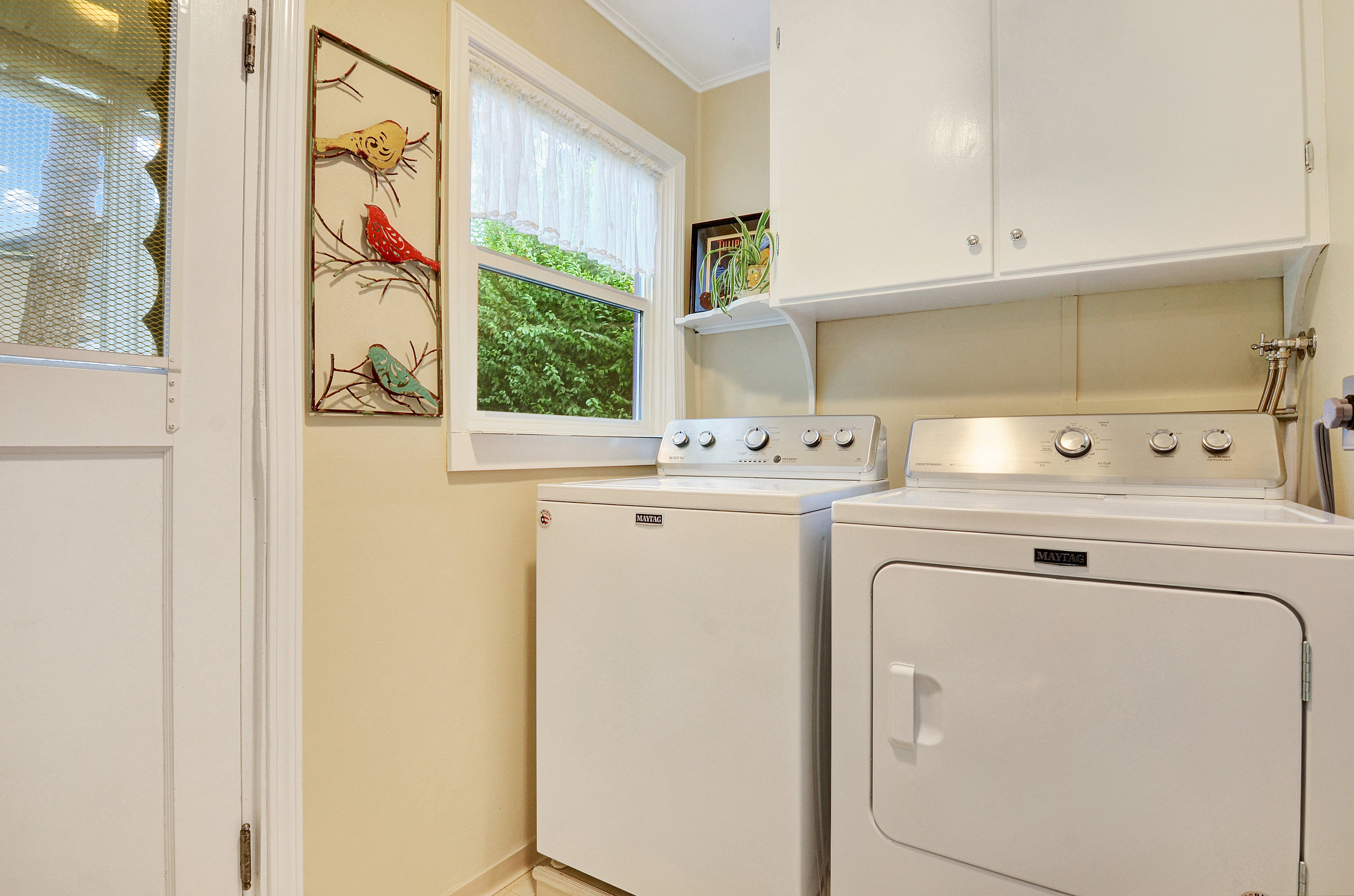 The laundry room is just a step down from the kitchen and dining area. Here you'll find a new floor, new washer and dryer, a door to the back yard, and a door on the right into the garage.