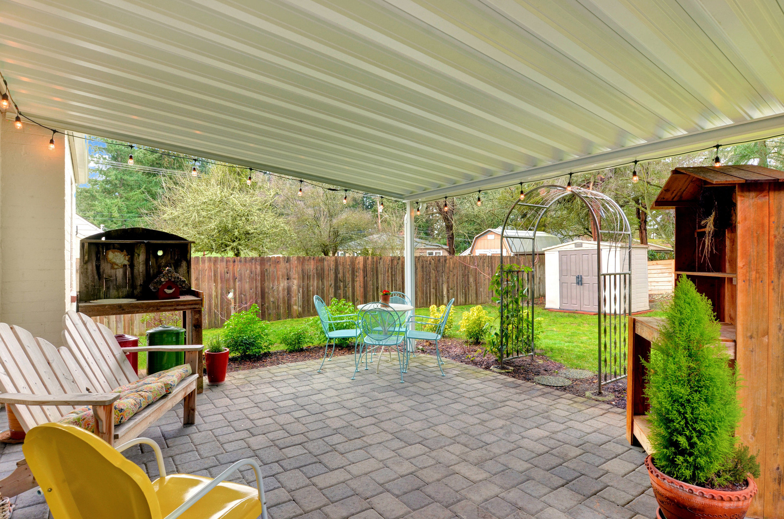 Set up your bbq, comfiest patio furniture, pretty potted plants, and enjoy. Step under the clematis growing on the arbor to reach the back lawn and storage shed.