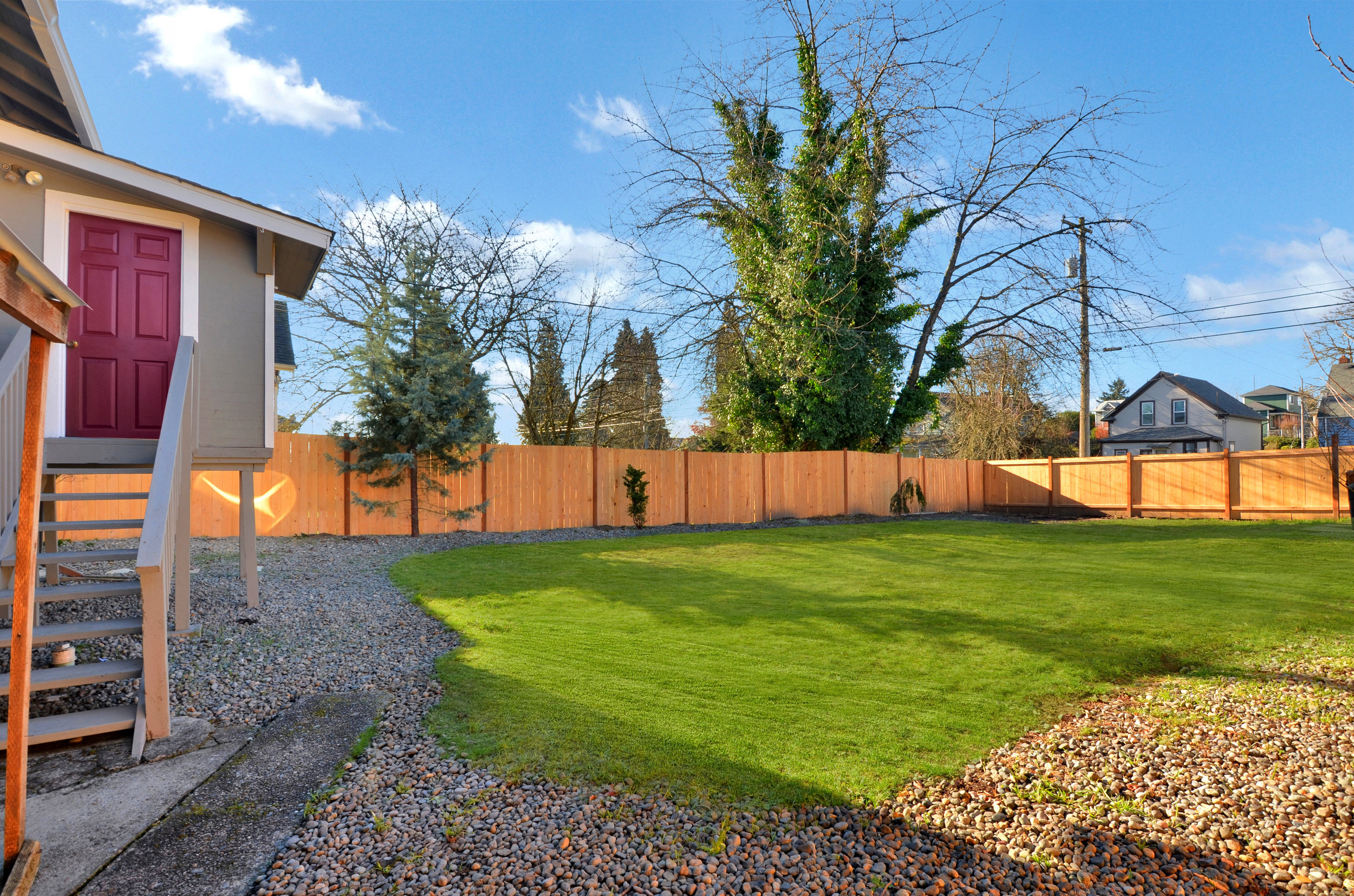 Brand new fencing fully encloses the back yard with its lawn, trees, and so much room for running and playing, or gardening.