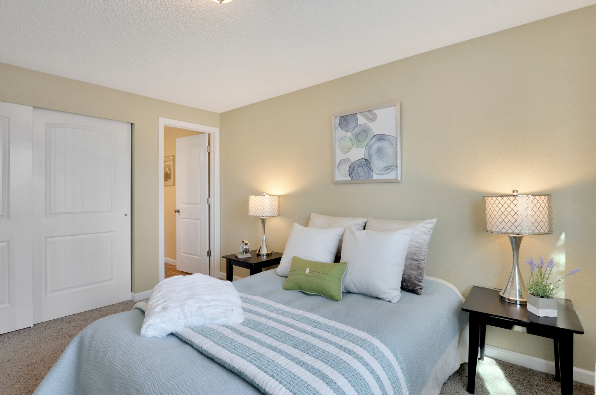 This en suite bedroom features a private 3/4 bath, large sliding closet doors, and the freshly painted walls found throughout the home.