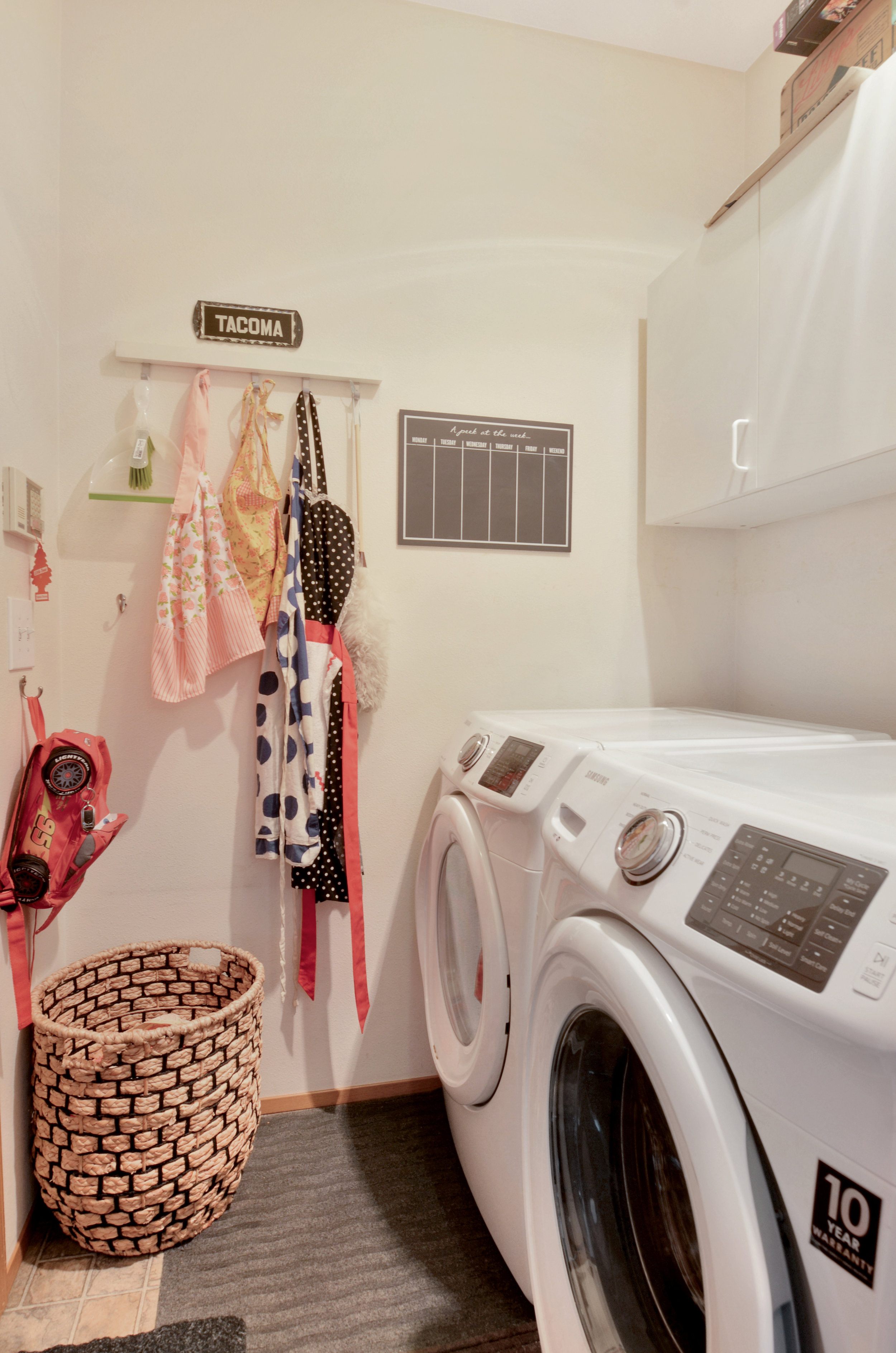 The laundry room is conveniently adjacent to the kitchen and includes cupboards over the washer and dryer. A door on the left leads into the 2 car garage.