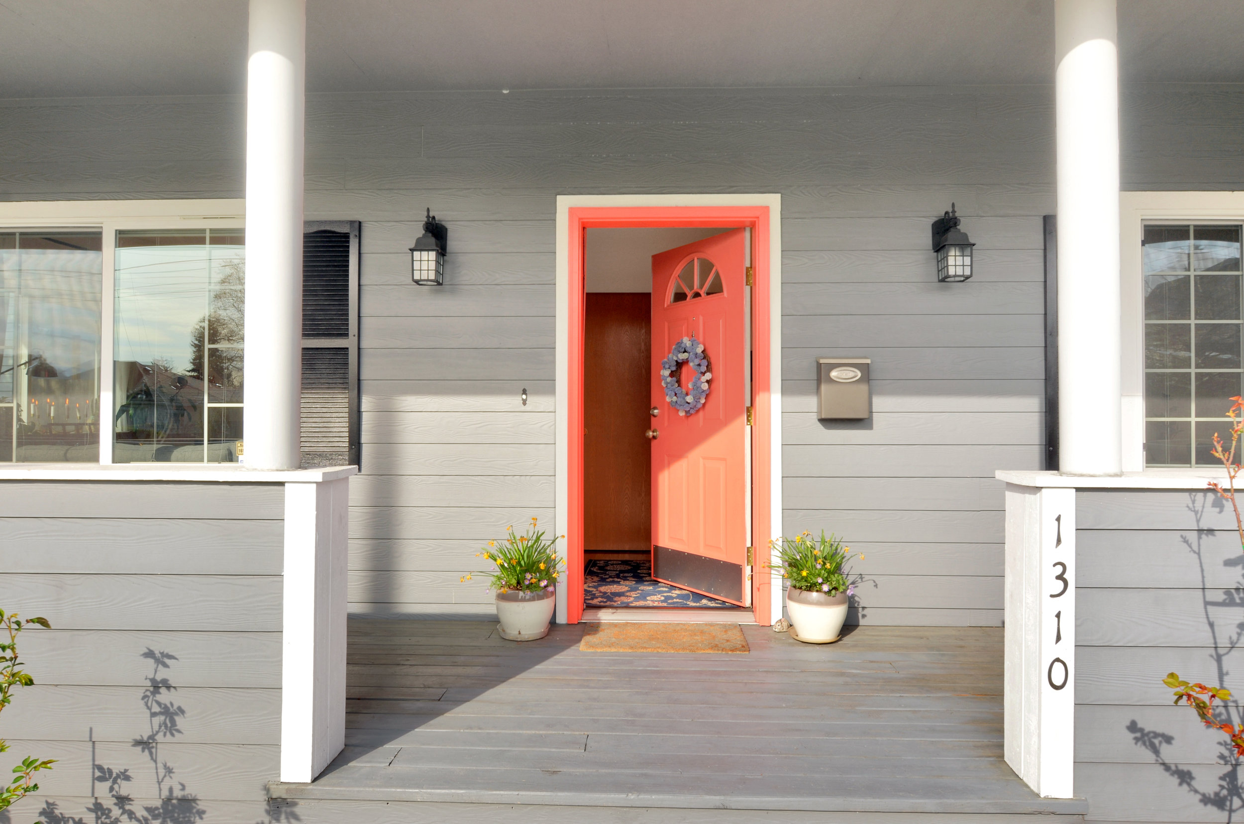 Another look at the welcoming, east facing covered porch with its bright door flanked by big windows.