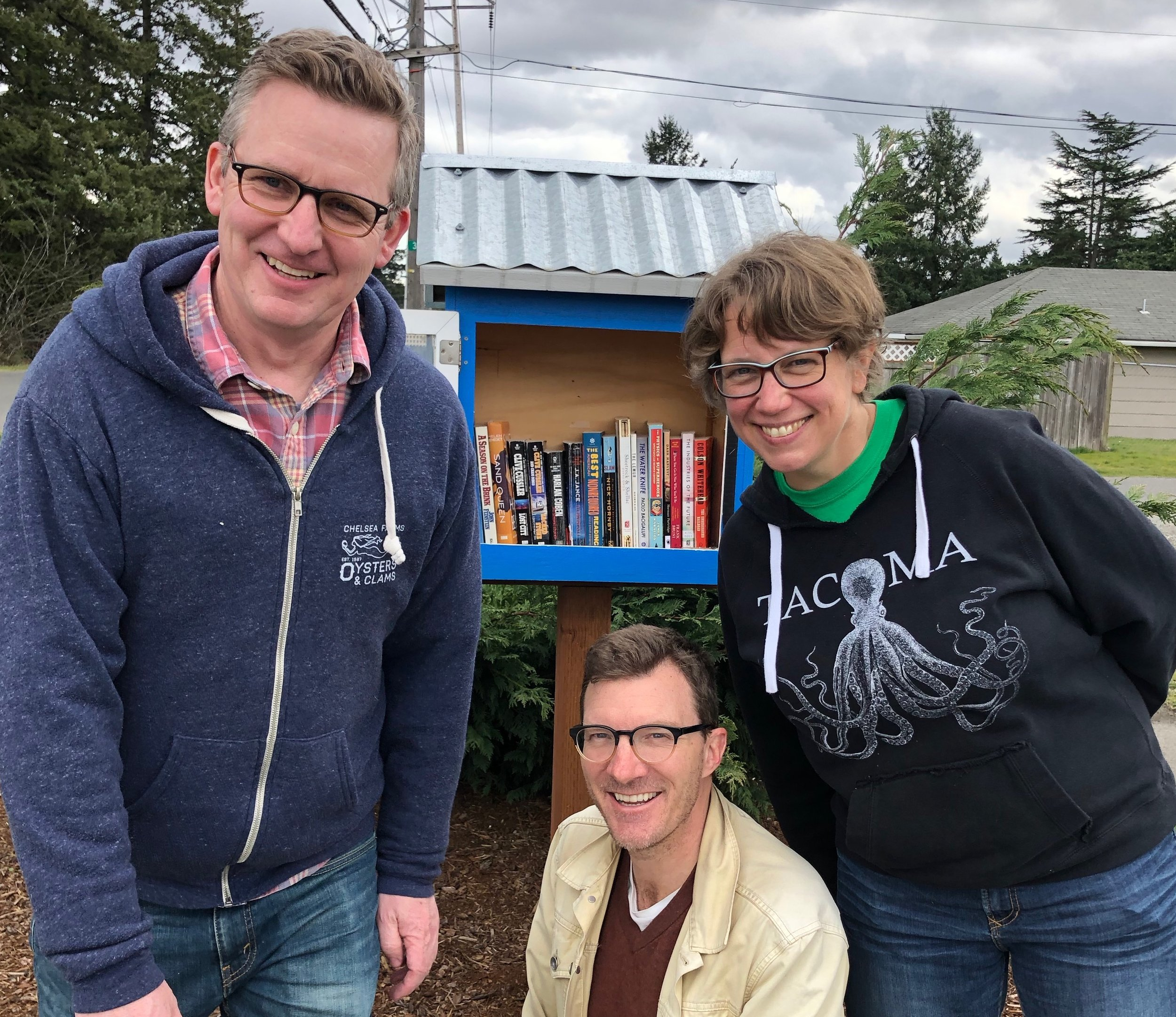 Meet Michelle Douglas of the Emergency Food Network crew and the Little Free Library they host in a diverse Lakewood neighborhood. Pictured with Michelle are Patrick Moreland and Steve Cathersal who come home to Tacoma to volunteer at the Emergency Food Network with Dr. Jamie!