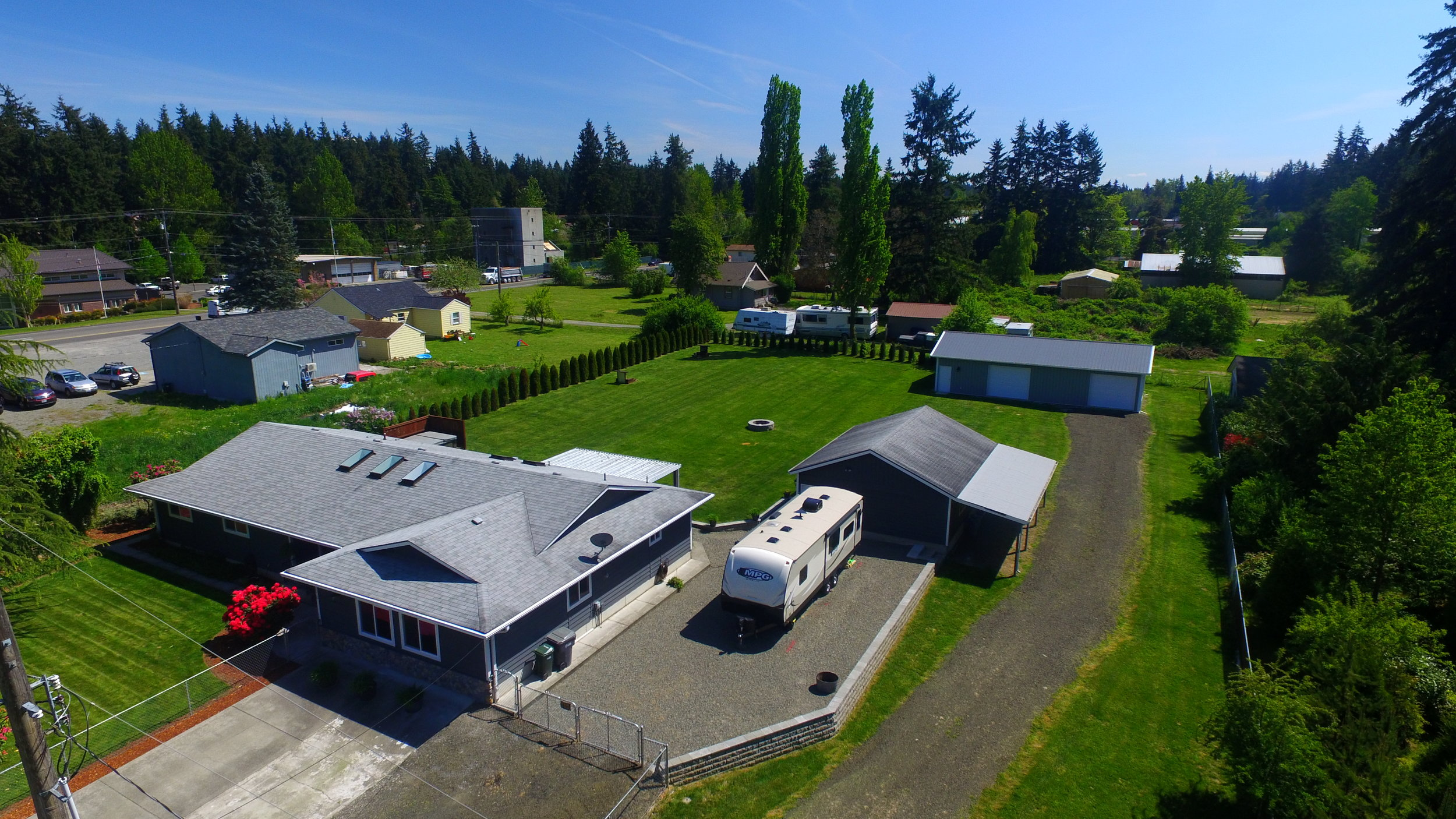 Lot includes 2 gated driveways, paved parking, detached garage with lean-to and upper storage area, new shop with 2 bay doors, covered patio, RV parking, pad & privacy screen & wiring for a hot tub, fencing, fruit trees, garden beds, fire pit, horseshoe pits, and a huge lawn.