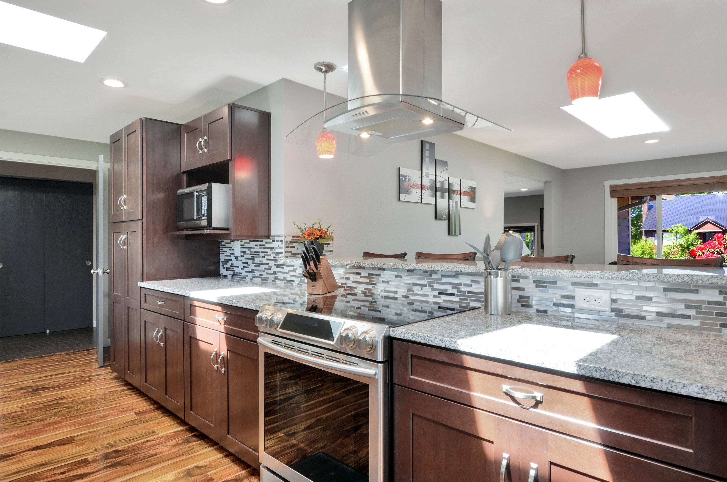 The remodeled kitchen features 2 skylights, slow-close drawers and cabinets, heat and stain resistant granite slab counters (with 10 year warranty), tile back splash, hood vent, and a full set of stainless appliances (homeowner can provide booklets for most of the appliances in the house).