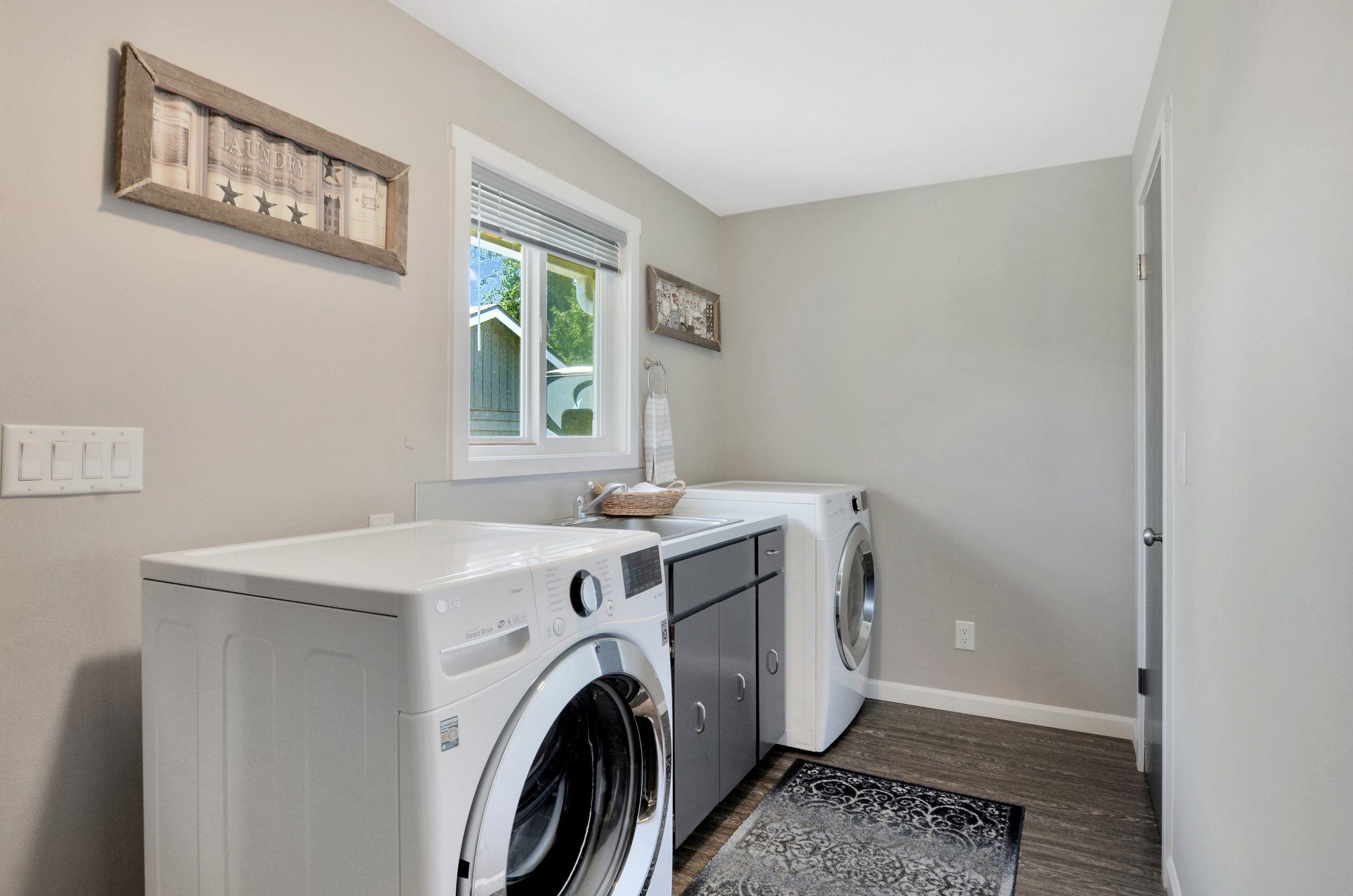 Last, but not least, for the interior is this laundry room with sink and cupboard storage as well as a door on the right to the 3rd bathroom. This bathroom features a stall shower and toilet, with sink just outside the door between the washer and dryer.