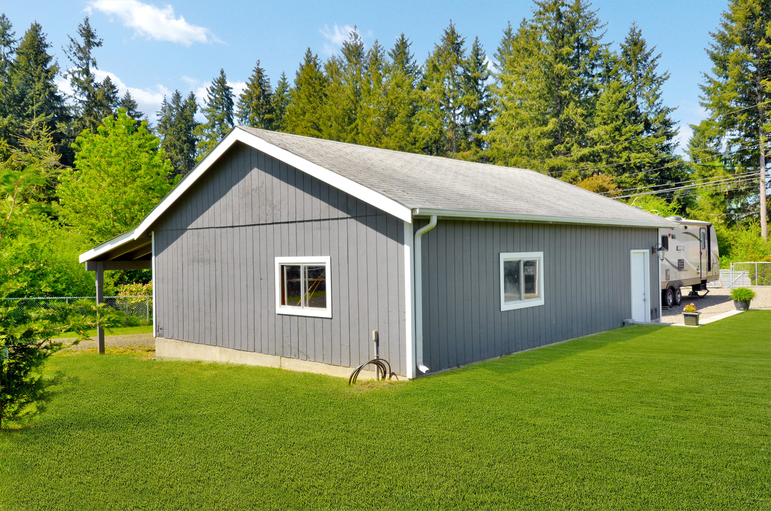 The detached 24 x 30 garage has a new bay door, a new man door, and an insulated ground floor, with a lean-to and upper level for additional storage.