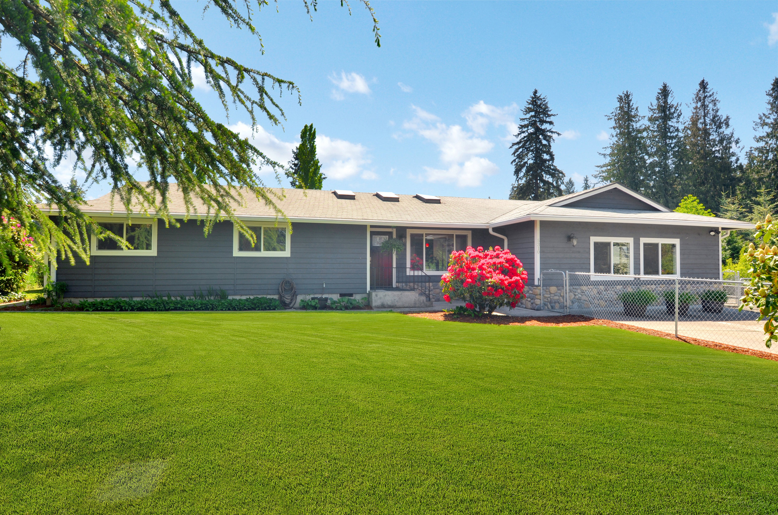The clean front lawn with beds bordering the house offer a wonderful welcome as you walk to the front door.