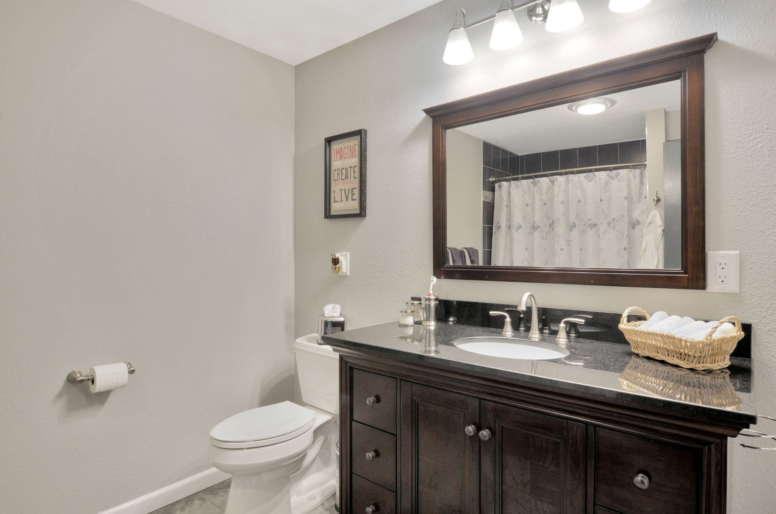 The full bath is found in the hall with the bedrooms and is easy to access from the main living space as well. This bath has a jacuzzi tub. Catch a glimpse of the tiled shower/jacuzzi bath in the mirror here.