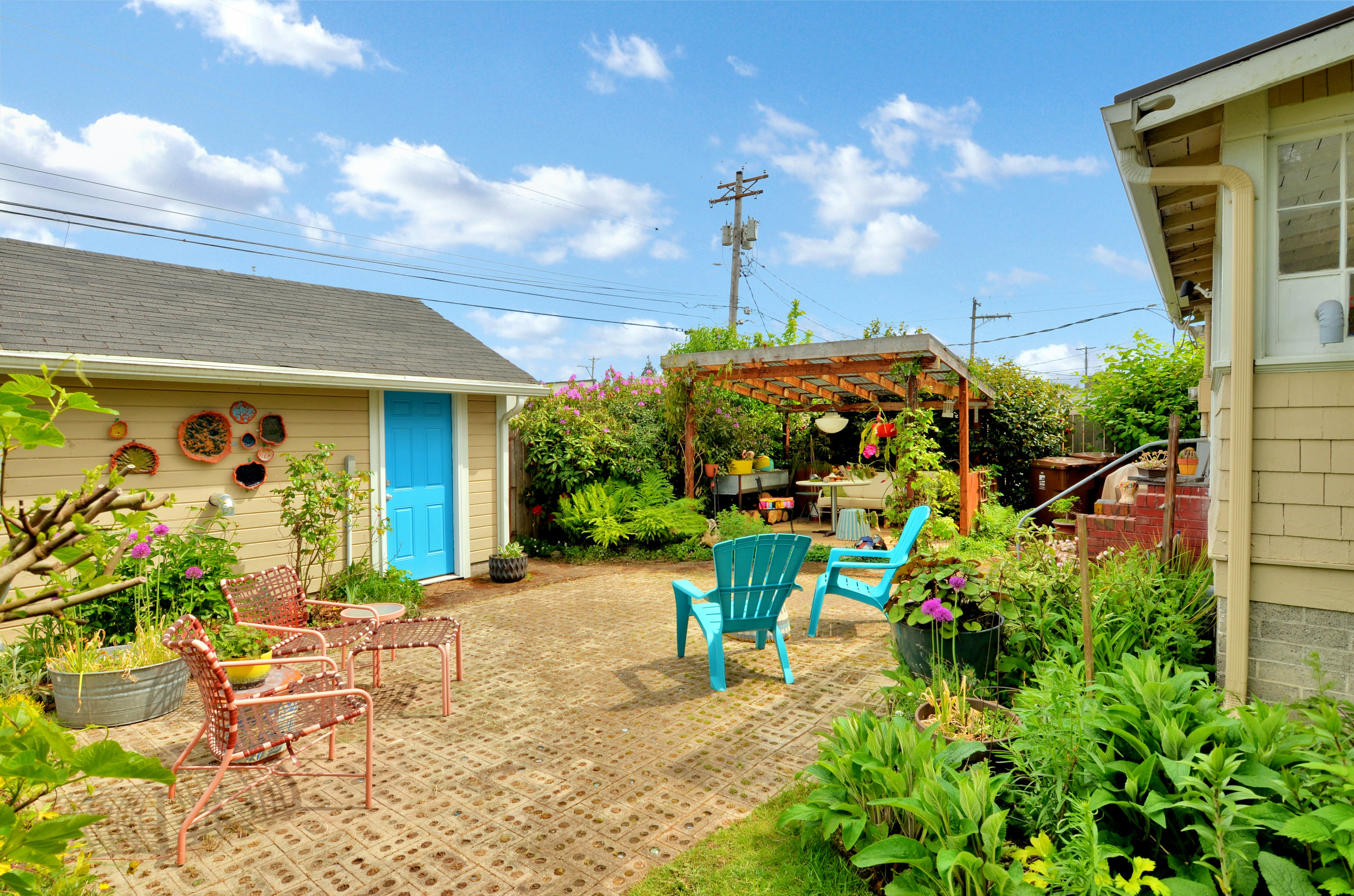 Lush flower beds and an inviting patio accompany the detached garage/studio in the back.
