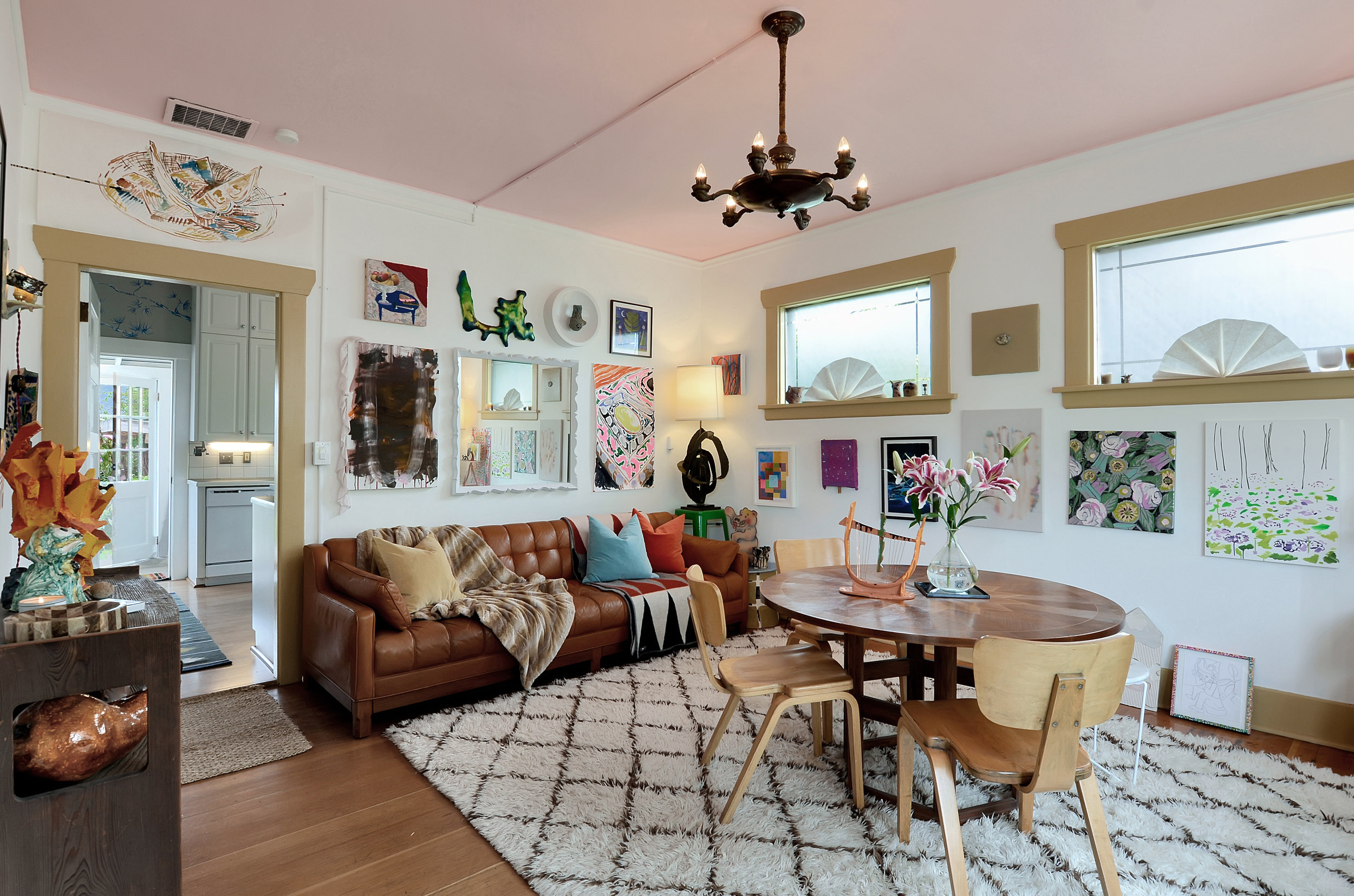 Tall ceilings, lots of natural light, and refinished fir floors create a comfortable living and dining area. The dreamy pink ceiling begs you to let a little fun and happiness into this room. So invite a friend over, lay the colorful rugs down, and open the front door for garden sounds.