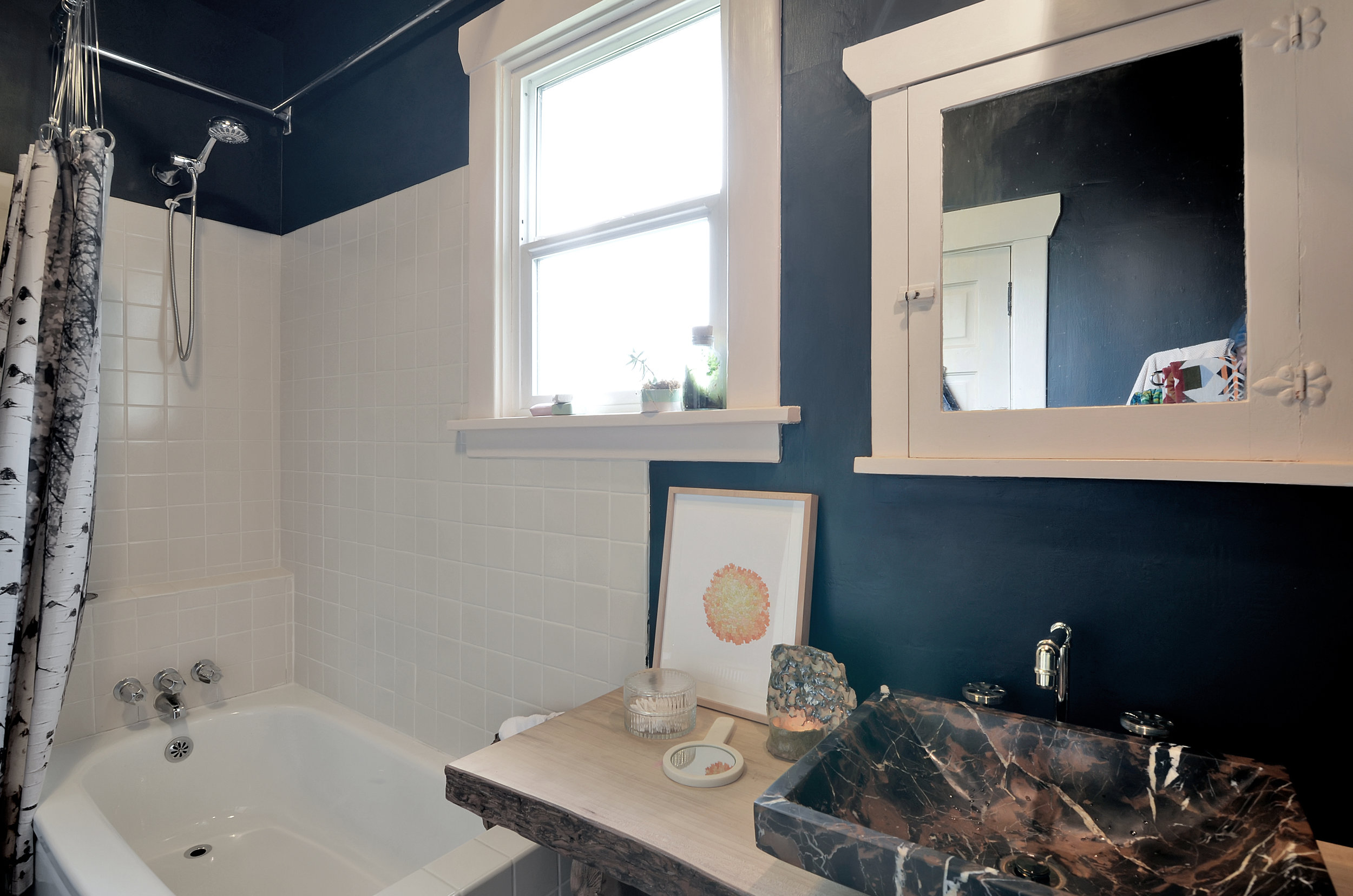 The renovated full bath is located on the main floor and features white tile, refinished fir floors, and a live-edge wooden counter with a stone vessel sink. This isn't your basic bathroom. It has style that combines rusticity with polish, light and warmth with beautiful moody shadow. As you can tell, we really like it.