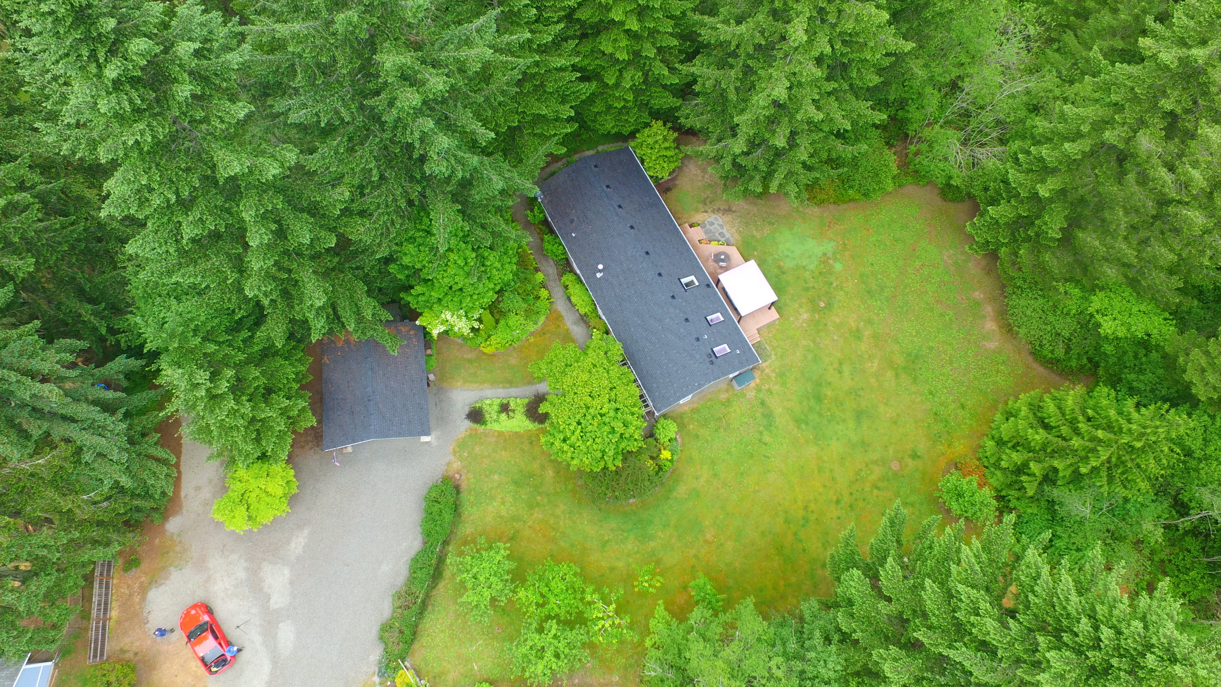 An aerial view of this 2.8 acre property with wooded trails, orchard, spacious lawn, RV parking, and a great view of that roof too.