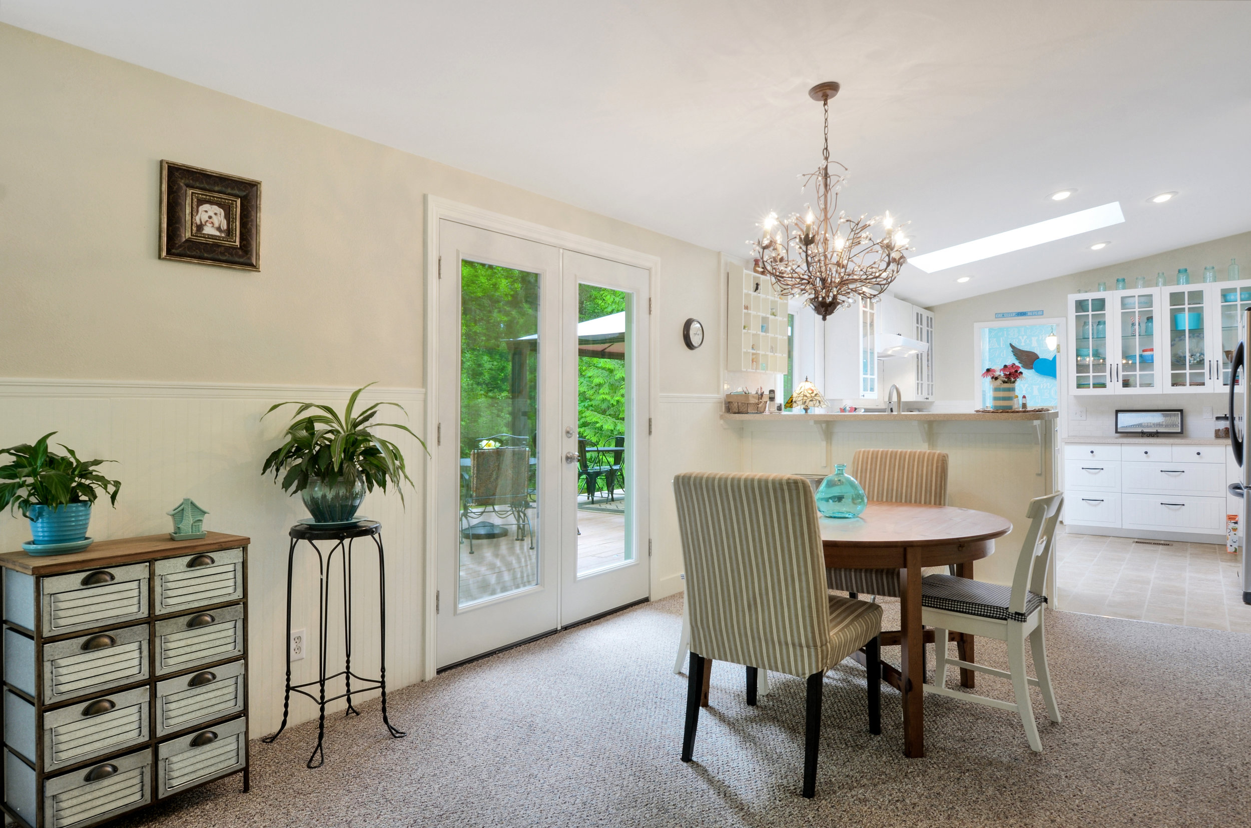 From the entry and front living room, step through to the dining area with its French doors out to the back yard and deck.