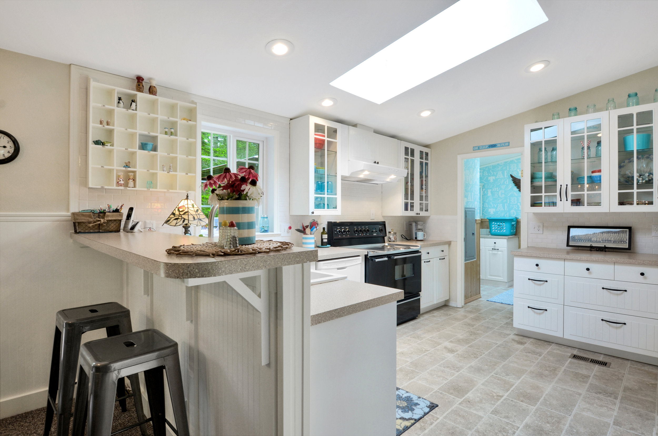 This kitchen is a beauty. With a window overlooking the back yard, a farmhouse sink, mini subway tile backsplash, and easy access to either the laundry room or the living and dining area. Pull a stool up to the kitchen bar counter for breakfast or a chat with the cook. This kitchen is all redone with a bright skylight, fresh counters, new cabinets and appliances (except for the stove which is a wonderful wide range with a griddle and warming oven!).