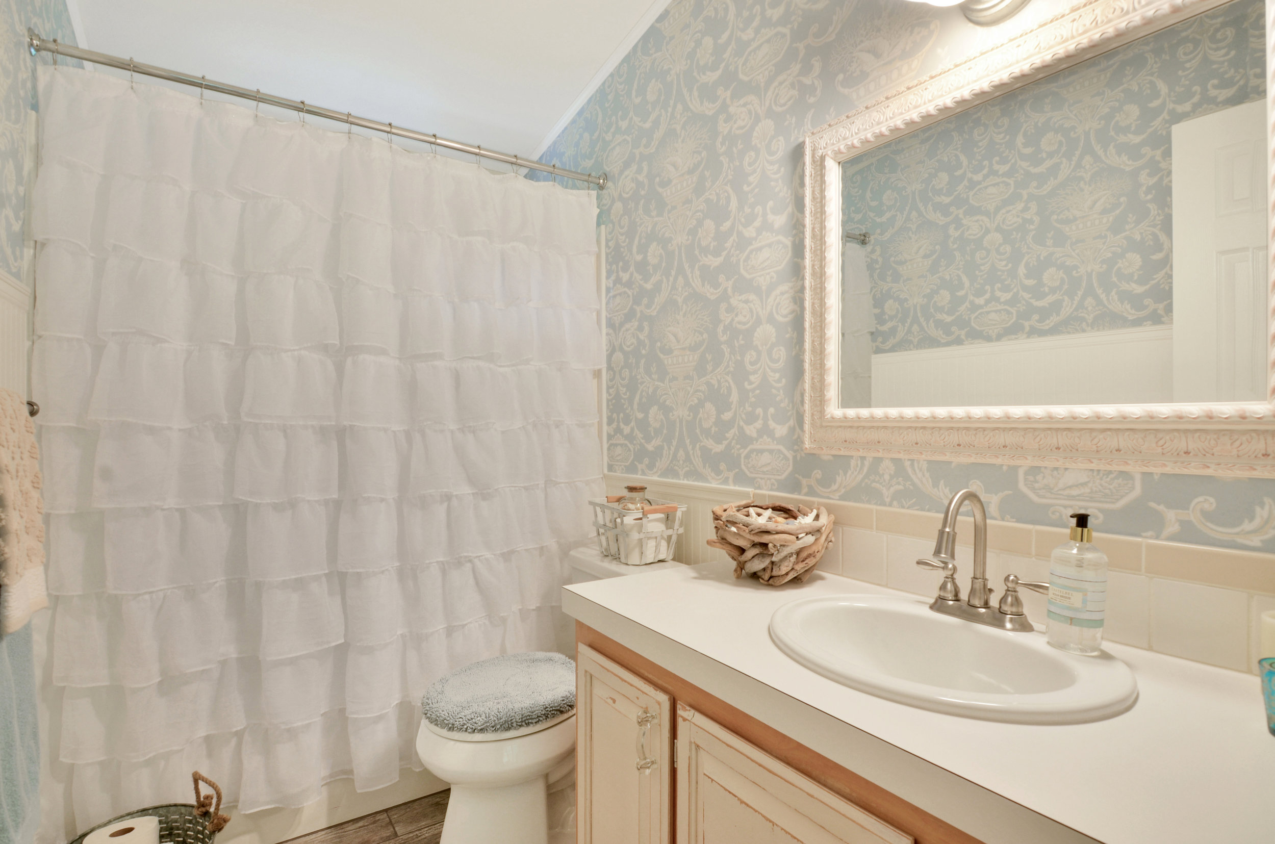 The 2nd full bath in the home is located off the family room between the 2 additional bedrooms. With a shower/bath combination, a spacious vanity, tasteful tile backsplash, and pretty design, this room is ready to go.